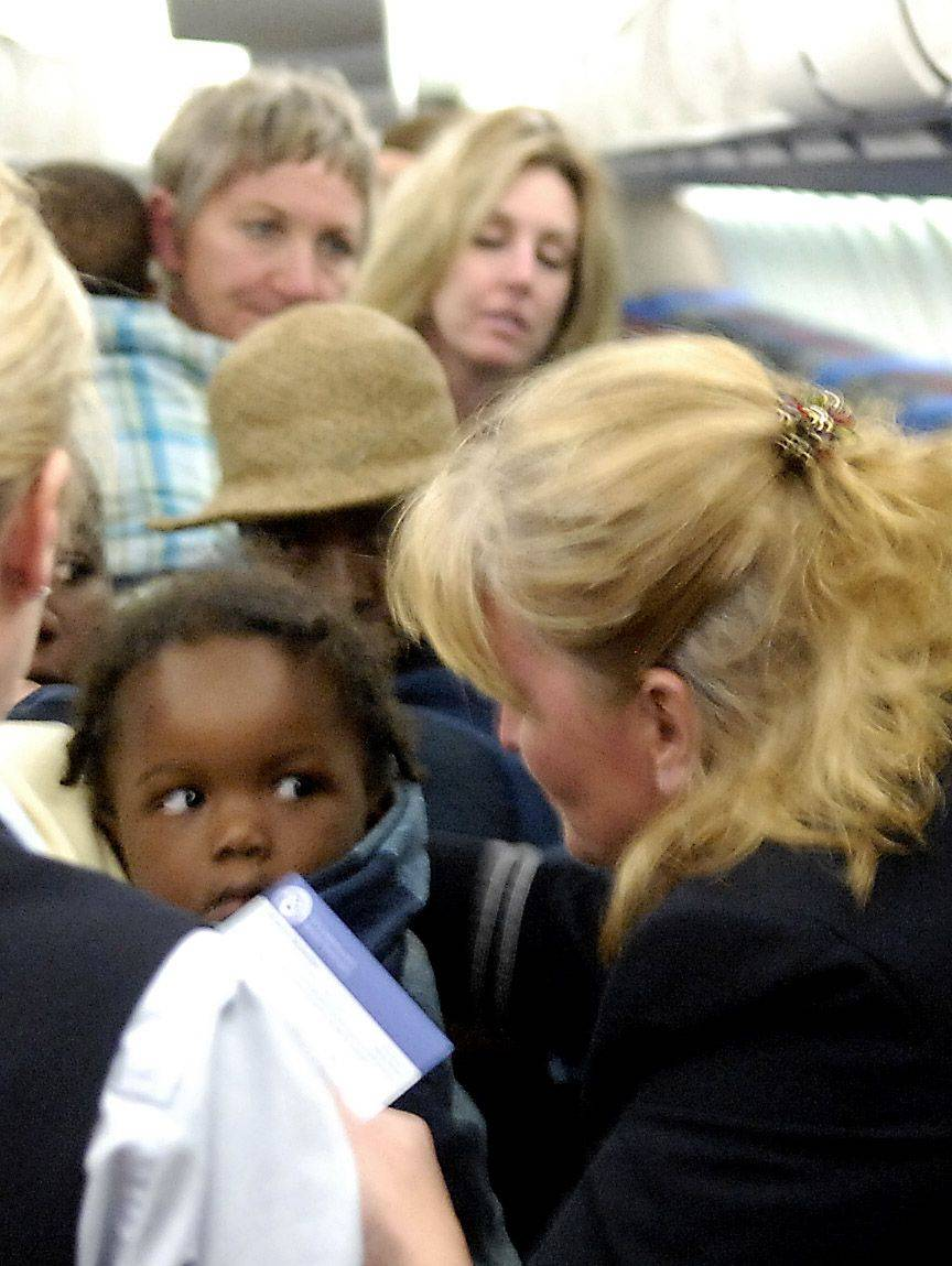 Flight attendant Corrine Hart-Cooley wraps a blanket around a child before deplaning in Chicago on United Airline's first relief trip to Haiti.