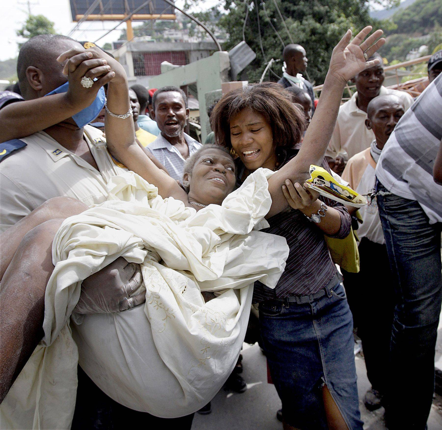 Gladys Loiuis Jeune is pulled alive from the rubble of her home in Port-au-Prince nearly 43 hours after the earthquake, where she was greeted by her ecstatic daughter Thursday, Jan. 14, 2010.