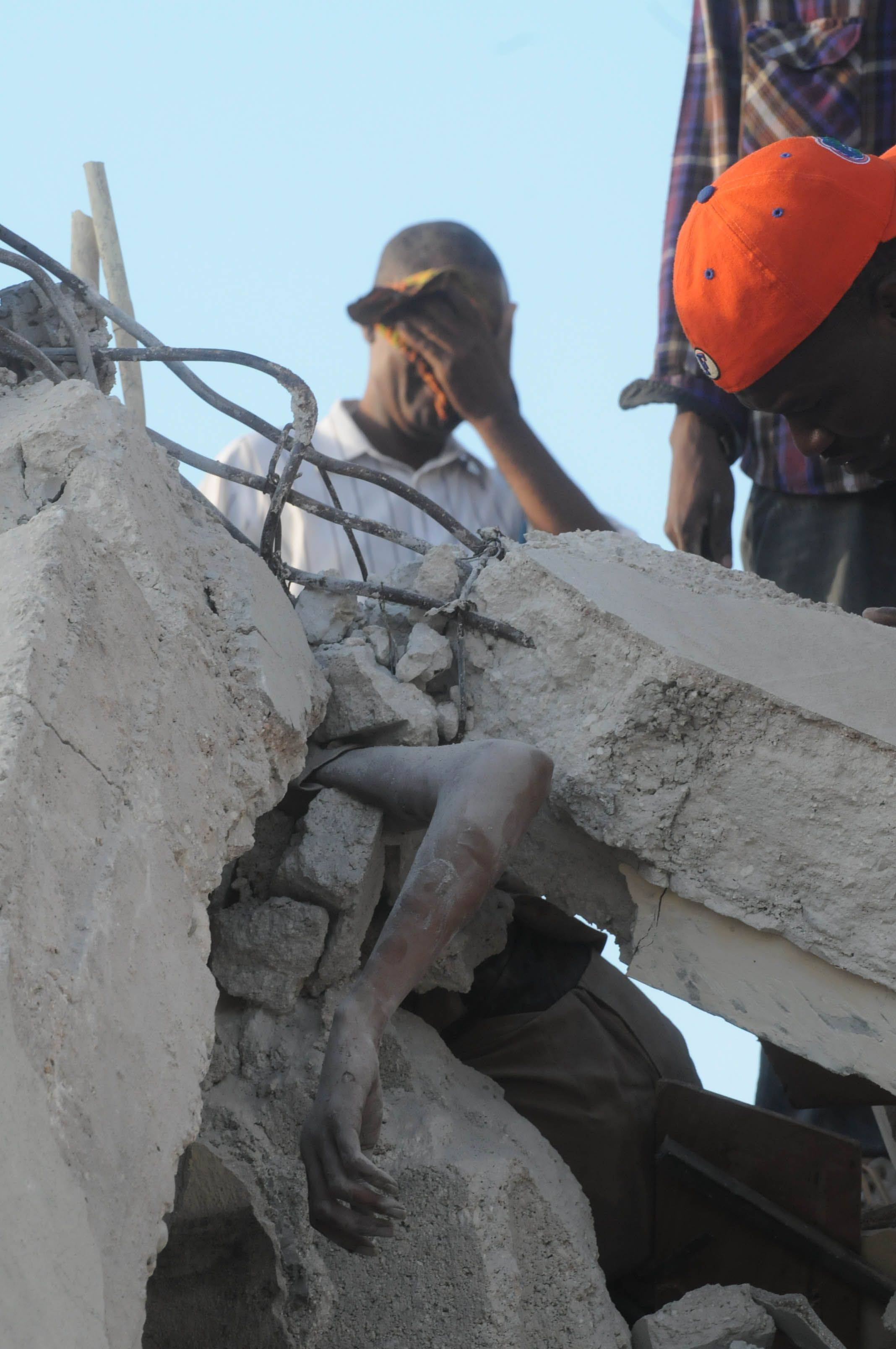 A man gestures behind a person trapped in the rubble of a collapsed building in Port-au-Prince Wednesday, Jan. 13, 2010.