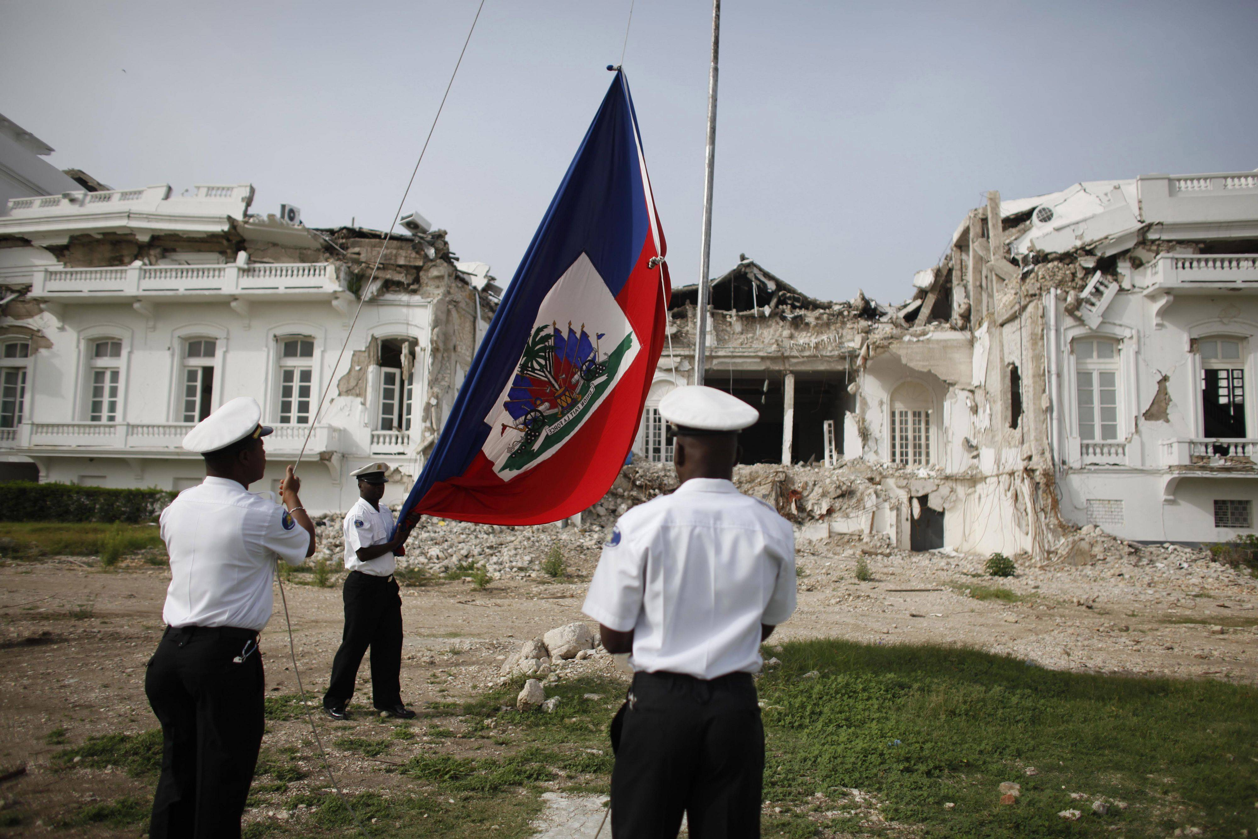 In this photo taken July 4, 2010, police raise the Haitian flag in front of the Jan. 12 earthquake damaged National Palace in Port-au-Prince, Haiti. Six months after the devastating earthquake several plans exist on paper to rebuild the main government buildings but no official decision has been made and the future of fifteen of the country's 17 ministry buildings that collapsed in the quake remains unclear.
