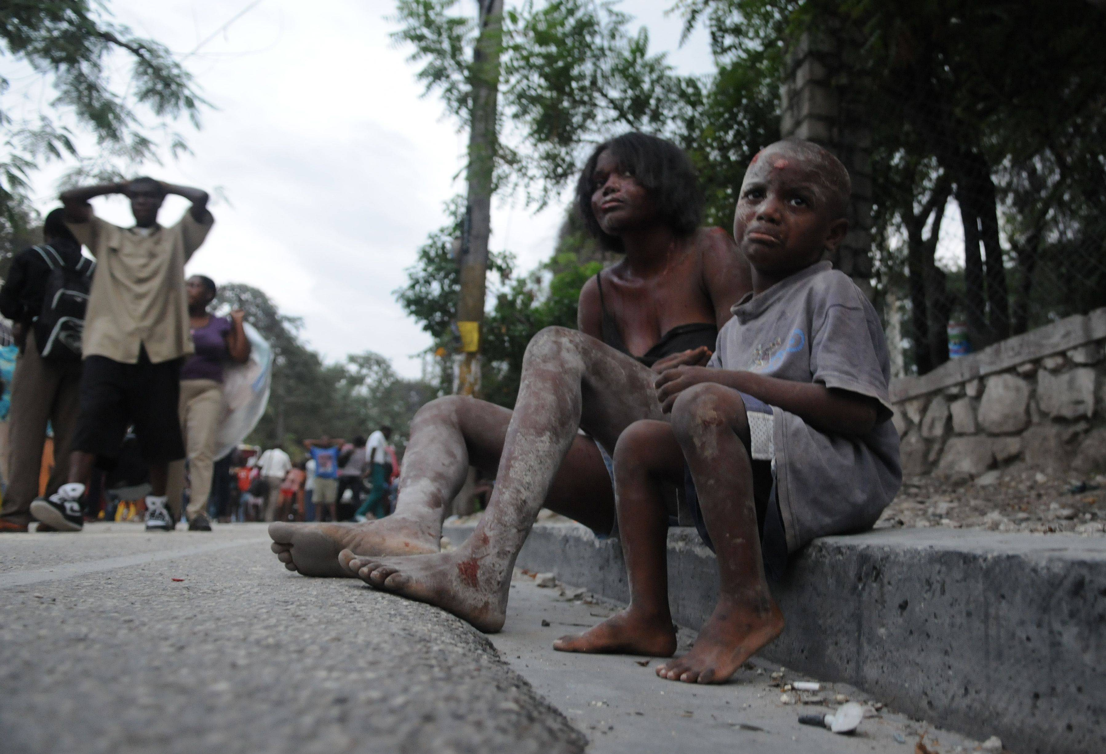 Injured people sit along Delmas road the day after an earthquake struck Port-au-Prince, Haiti, Wednesday, Jan. 13, 2010.