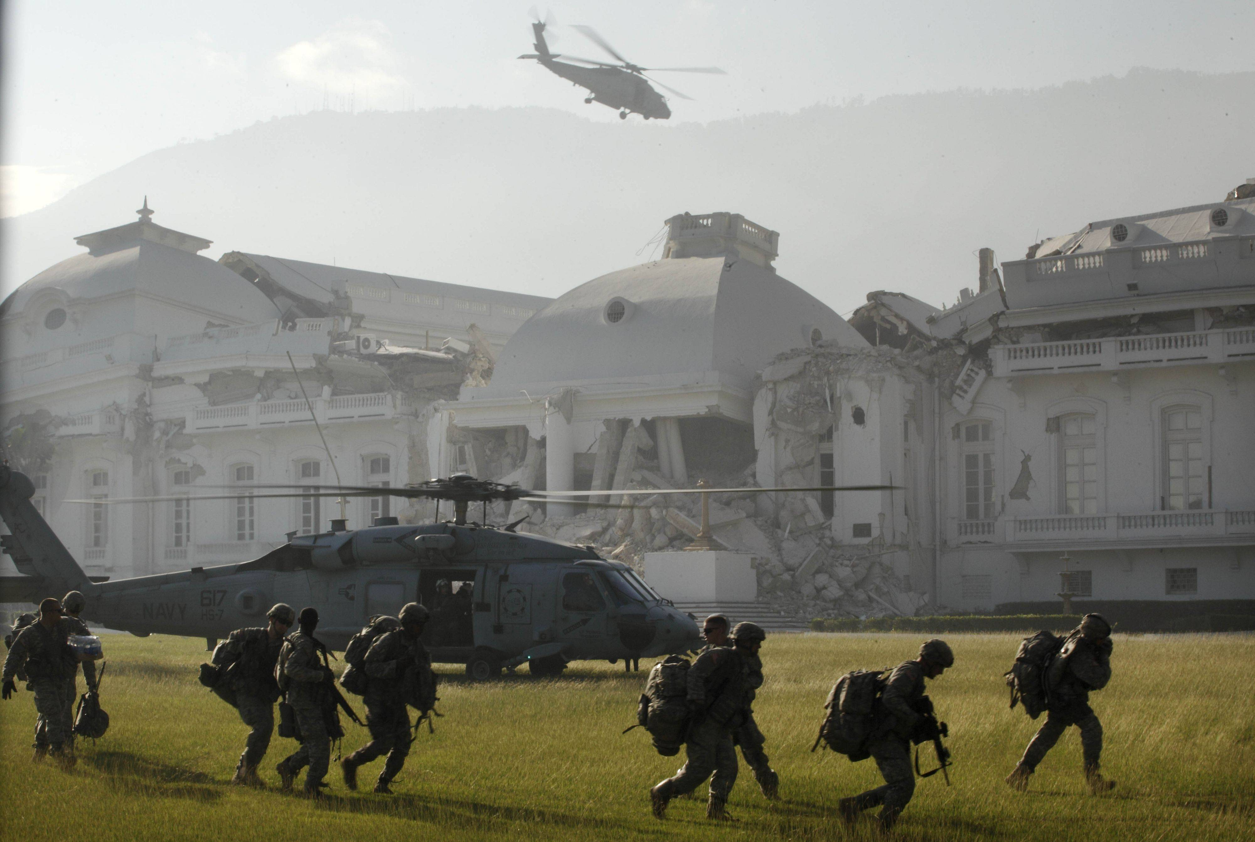 In this Jan. 19, 2010 file photo, a U.S. Navy helicopter takes off in front of the National Palace after members of the U.S. Army 82nd Airborne, front, landed in Port-au-Prince.