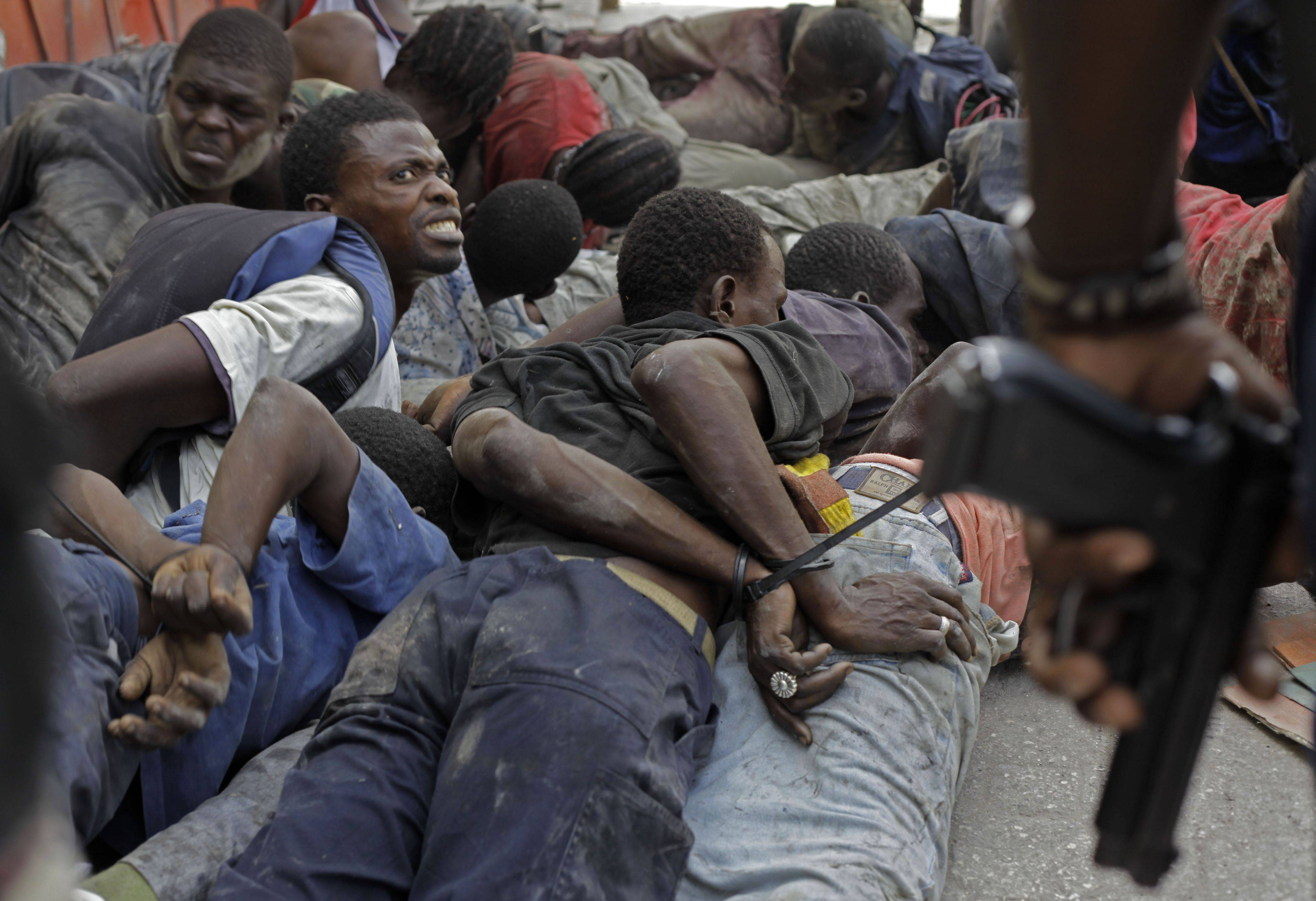 In this Feb. 6, 2010 file photo, a suspected looter looks at a Haitian police officer as he lies on the ground with his hands tied behind his back with other detained men after being caught in a bank in the aftermath of Haiti's earthquake in Port-au-Prince.