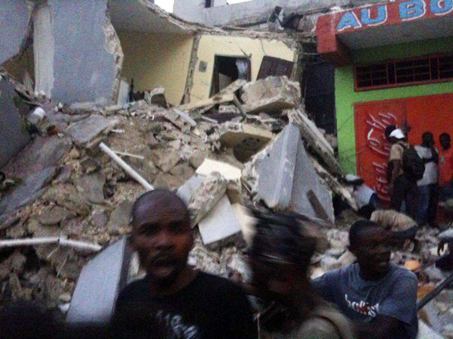 This photo provided by Carel Pedre shows people running past rubble of a damaged building in Port-au-Prince, Haiti, Tuesday, Jan. 12, 2010. The largest earthquake ever recorded in the area shook Haiti on Tuesday, collapsing a hospital where people screamed for help.