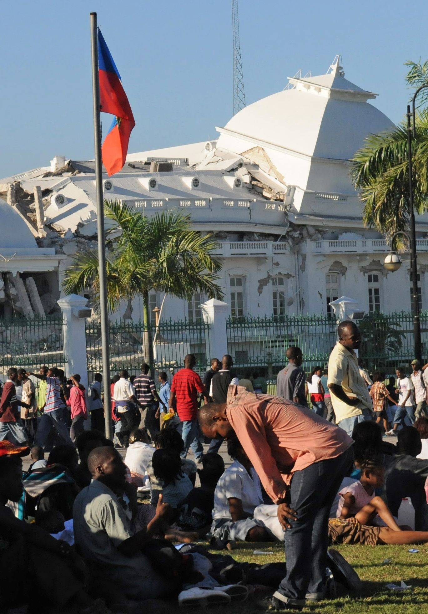 People gather outside Haiti's National Palace which was damaged by an earthquake in Port-au-Prince, Haiti, Wednesday, Jan. 13, 2010.