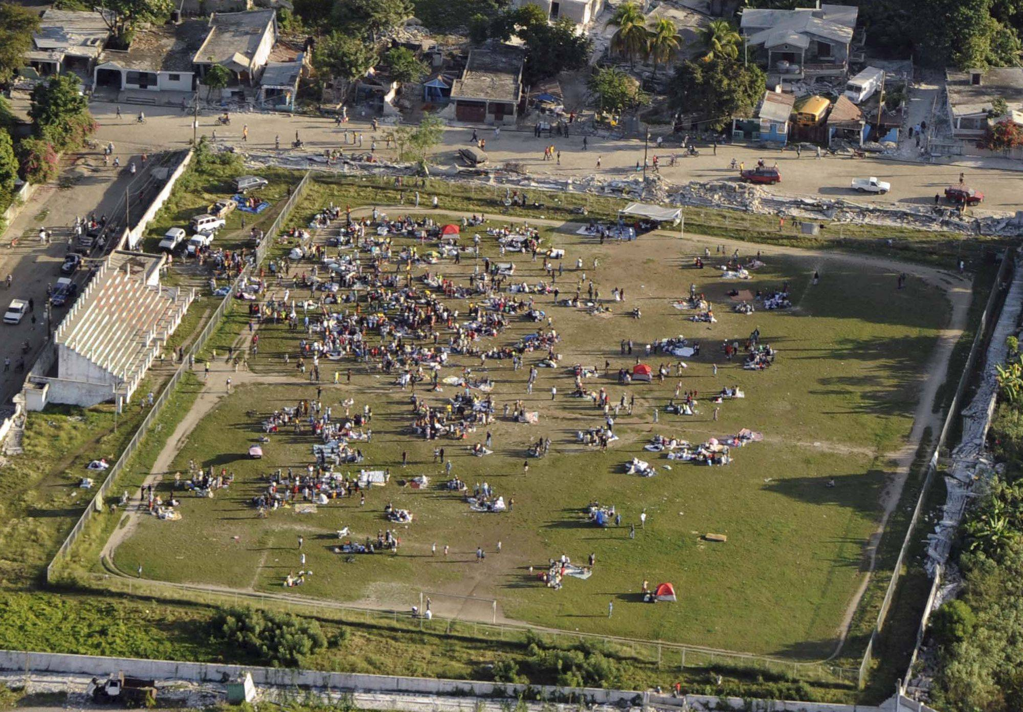 In this photo provided by the U.S. Coast Guard, people congregate in an empty field in Port-au-Prince, Haiti, Wednesday Jan. 13, 2009. The assessment follows a 7.0 magnitude earthquake that damaged the region Jan. 12.