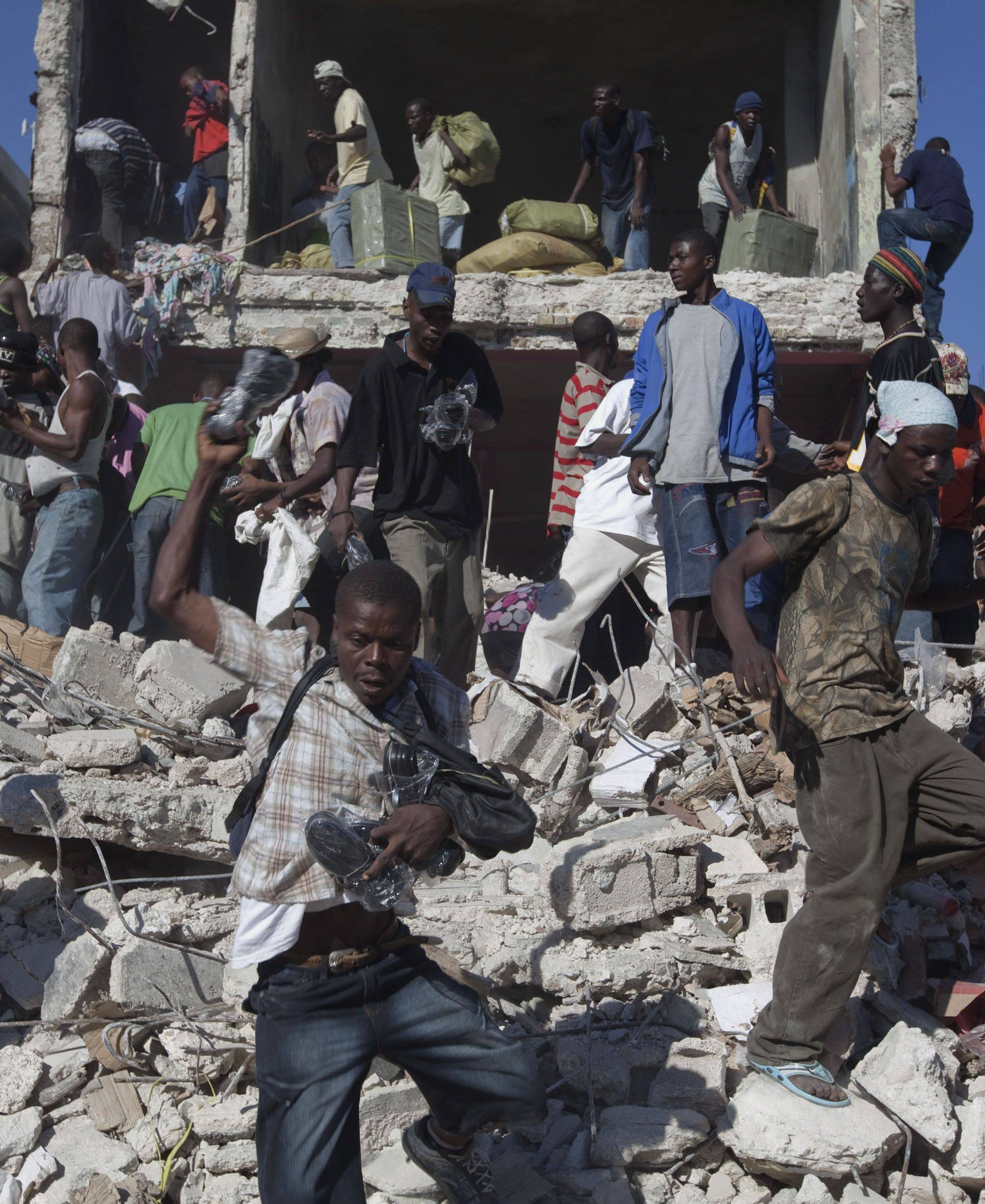 Scavengers look for goods amid the rubble of collapsed buildings in Port-au-Prince, Friday, Jan. 15, 2010.