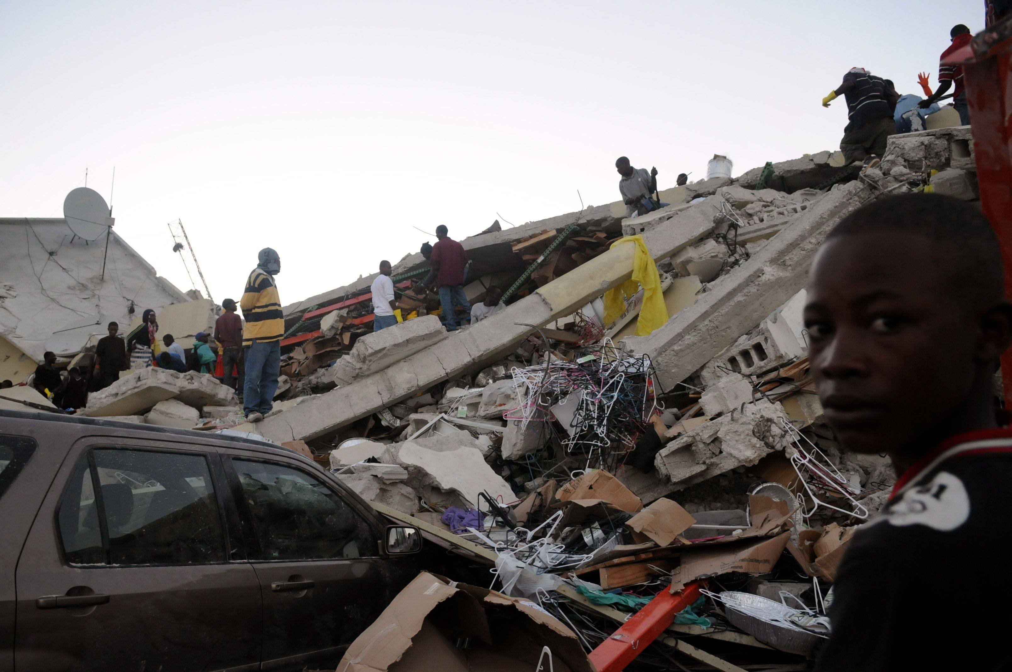 People stand on rubble along Delmas road the day after an earthquake hit Port-au-Prince, Haiti, Wednesday, Jan. 13, 2010.