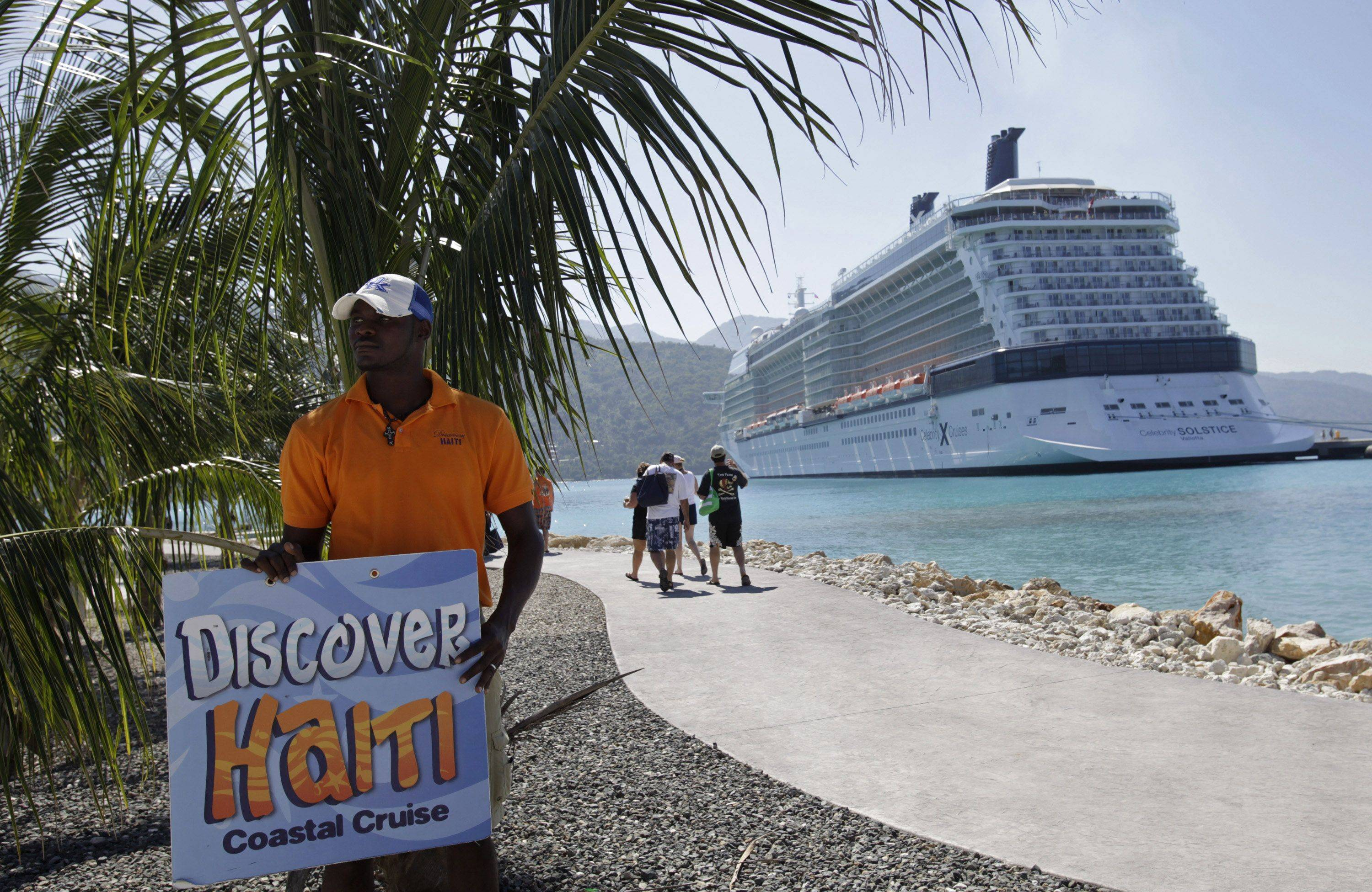 Joseph Philibert holds a sign to offer day trips to passengers from the Celebrity Cruises ship Solstice in Labadee, Haiti, Friday, Jan. 22, 2010.