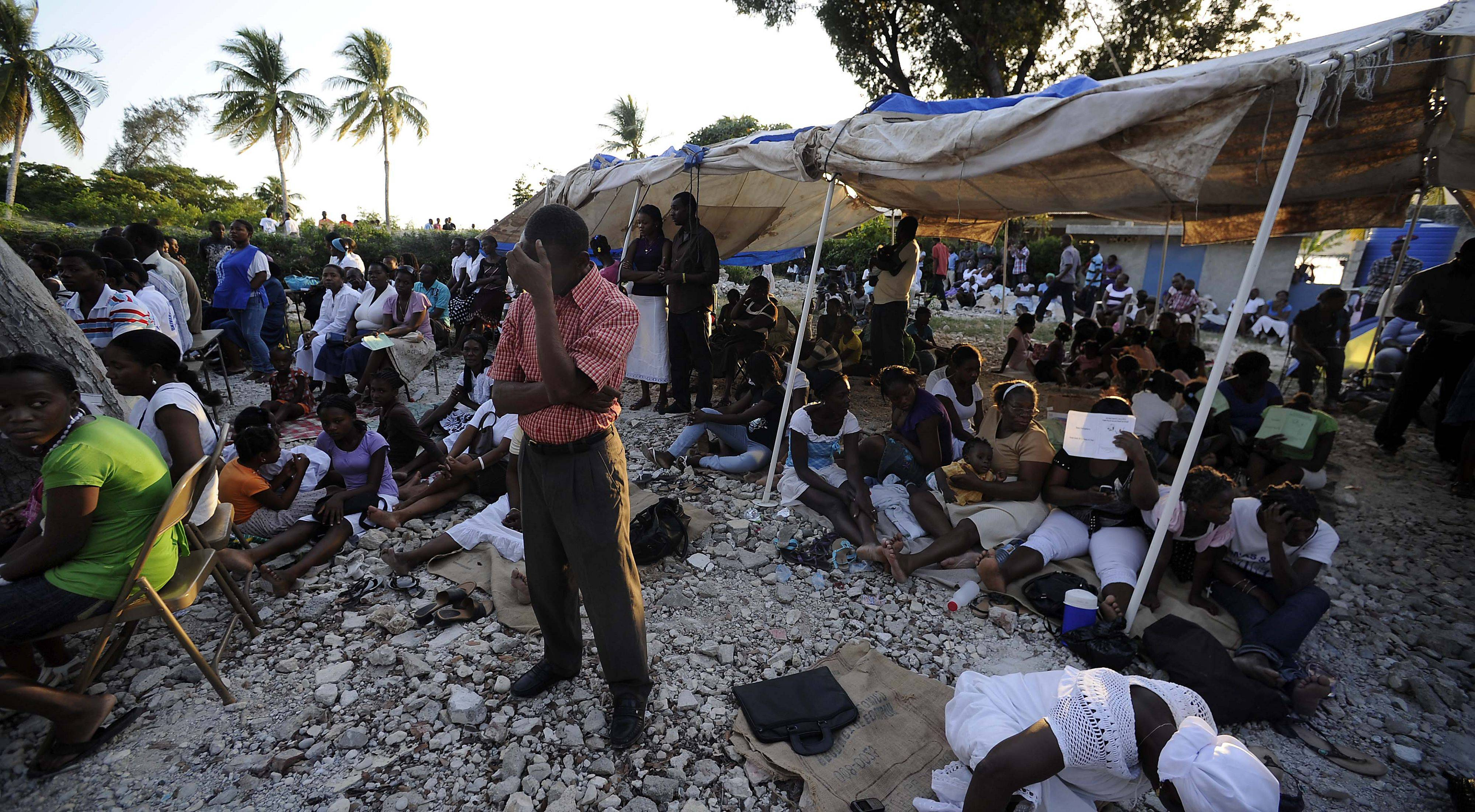 Praying in the middle of over a thousand Catholic worshipers, a Haitian man observes the one year anniversary of the earthquake that killed over 300,000 people.