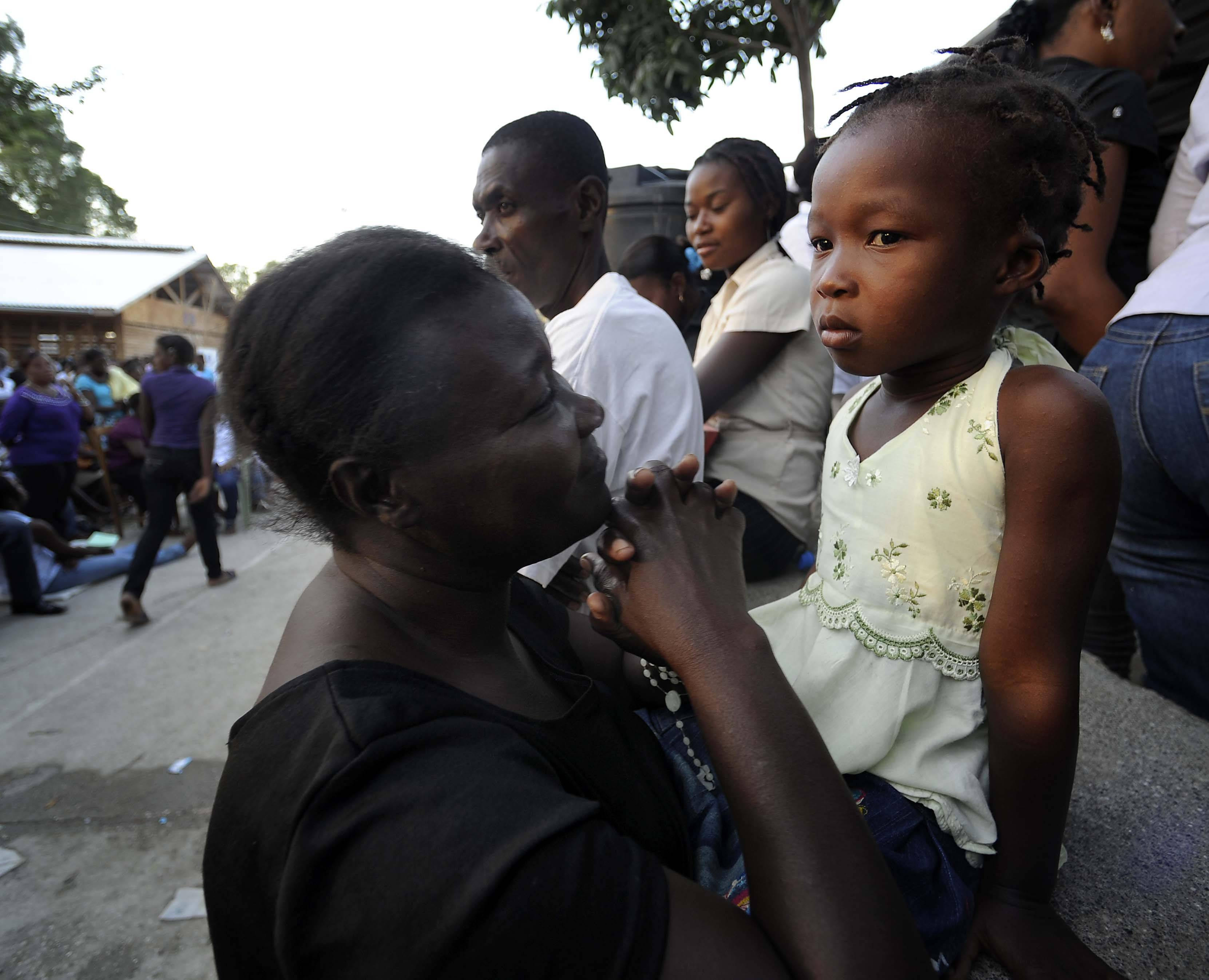 During a Catholic mass In Jacmel, Haiti a mother looks lovingly at her daughter as she prays on the first anniversary of the massive earthquake.