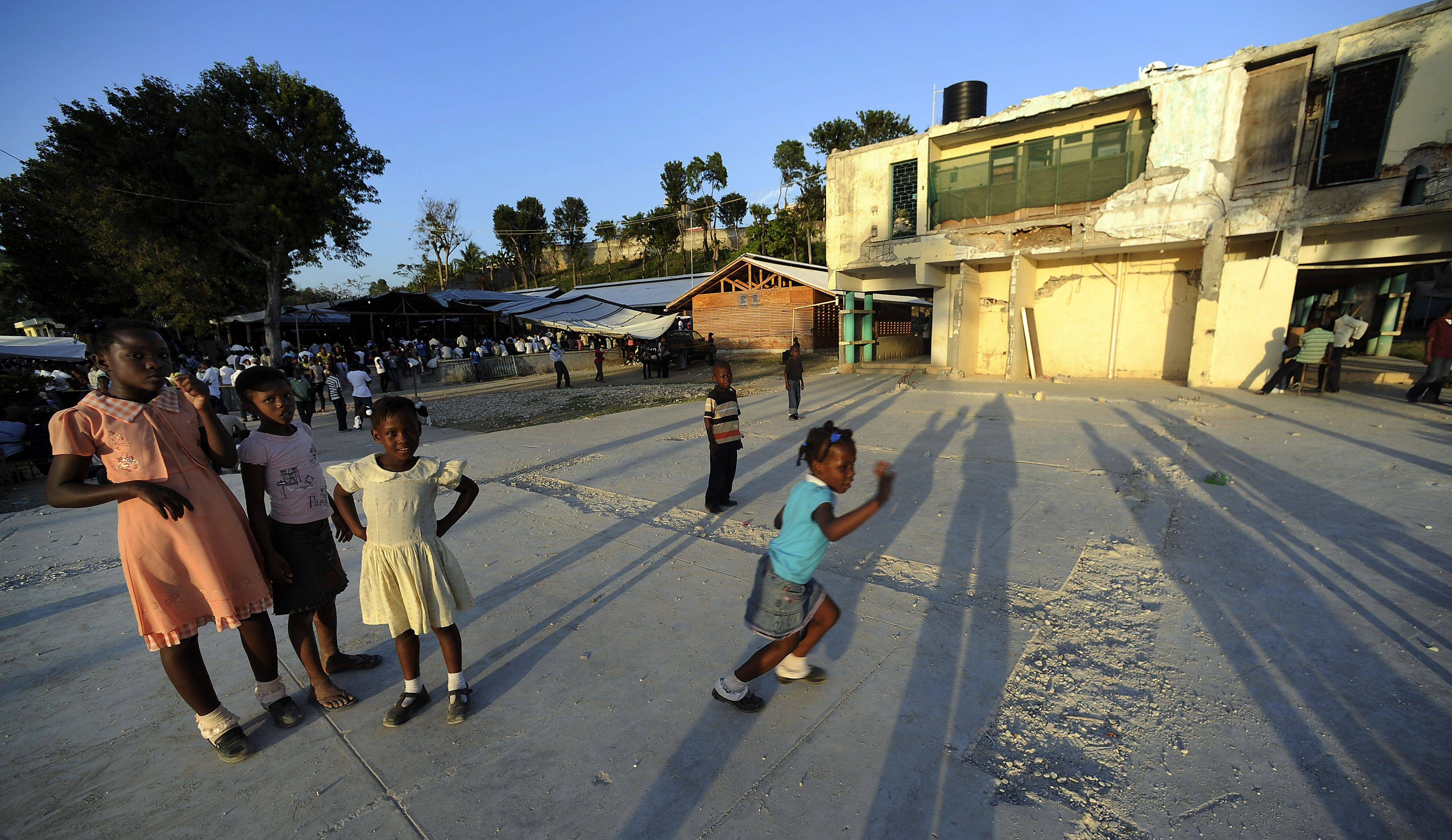 Haitian children dressed in their Sunday best play on what was a school that was destroyed by the earthquake of 2010.