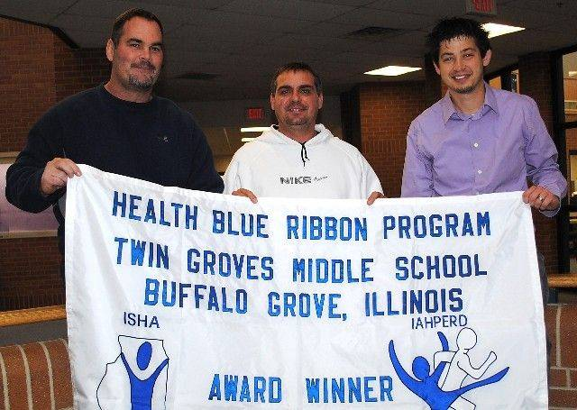 Proudly helping display the banner proclaiming IAHPERD Blue Ribbon recognition of the District 96 Twin Groves Middle School health program, from left, are physical education teachers Kevin McThenia and Jeff Cummings and health teacher Ben Leven.