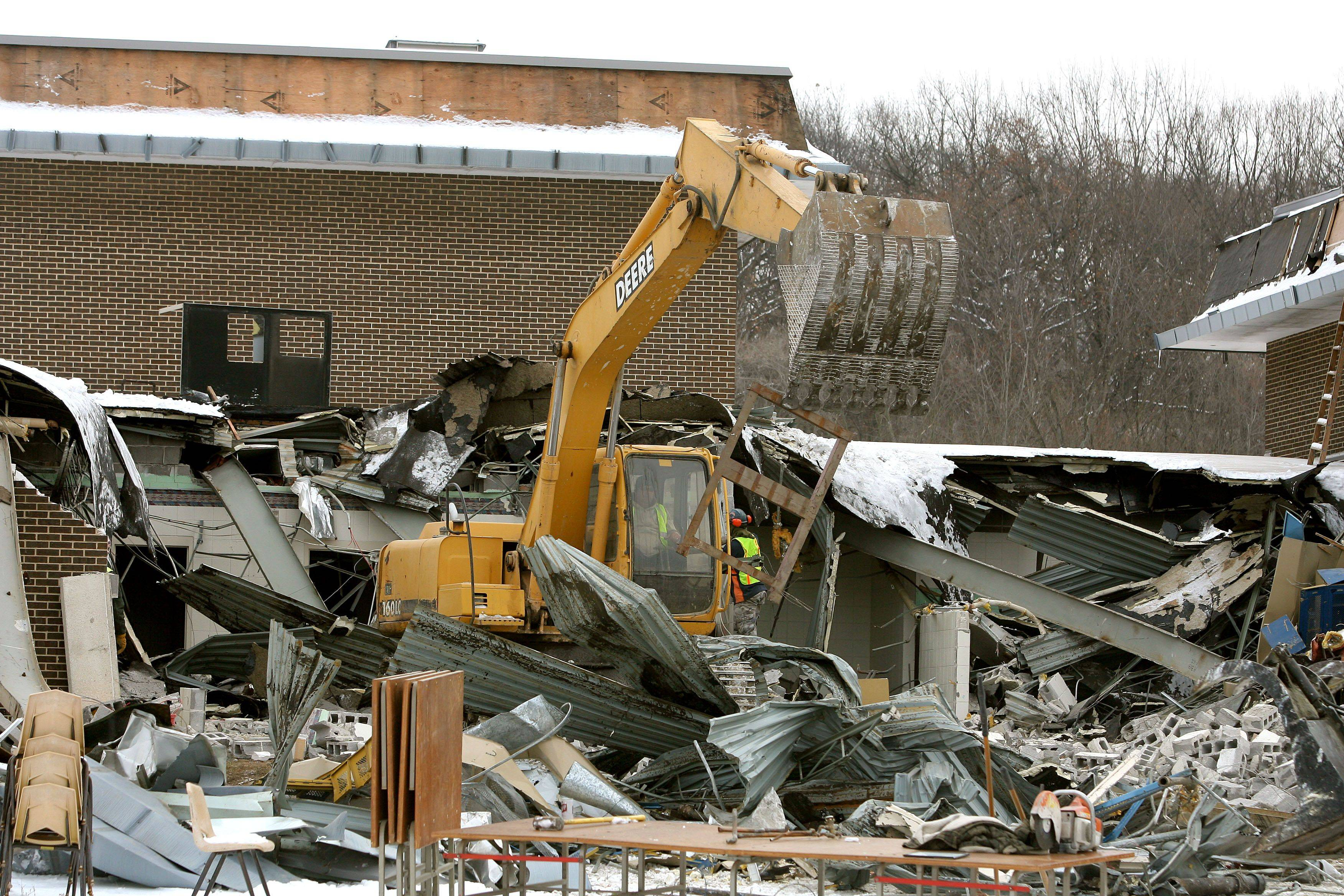 Demolition crews tear down the former Taveirne Middle School at routes 12 and 134 in Fox Lake Thursday morning.