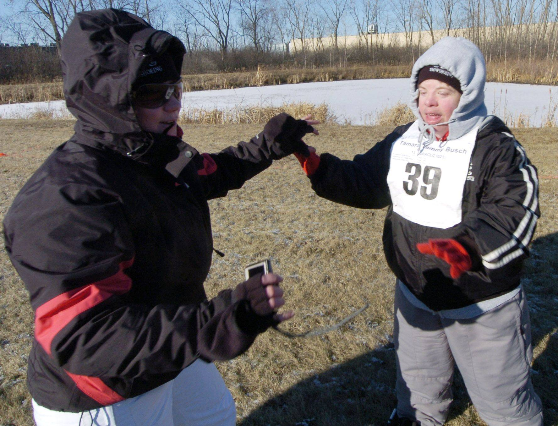 Tammy Busch, right of the Special Recreation Association of Central Lake County gets a high-five from coach Kelly Weber during Saturday's Special Olympics snowshoeing event at Lambs Farm.