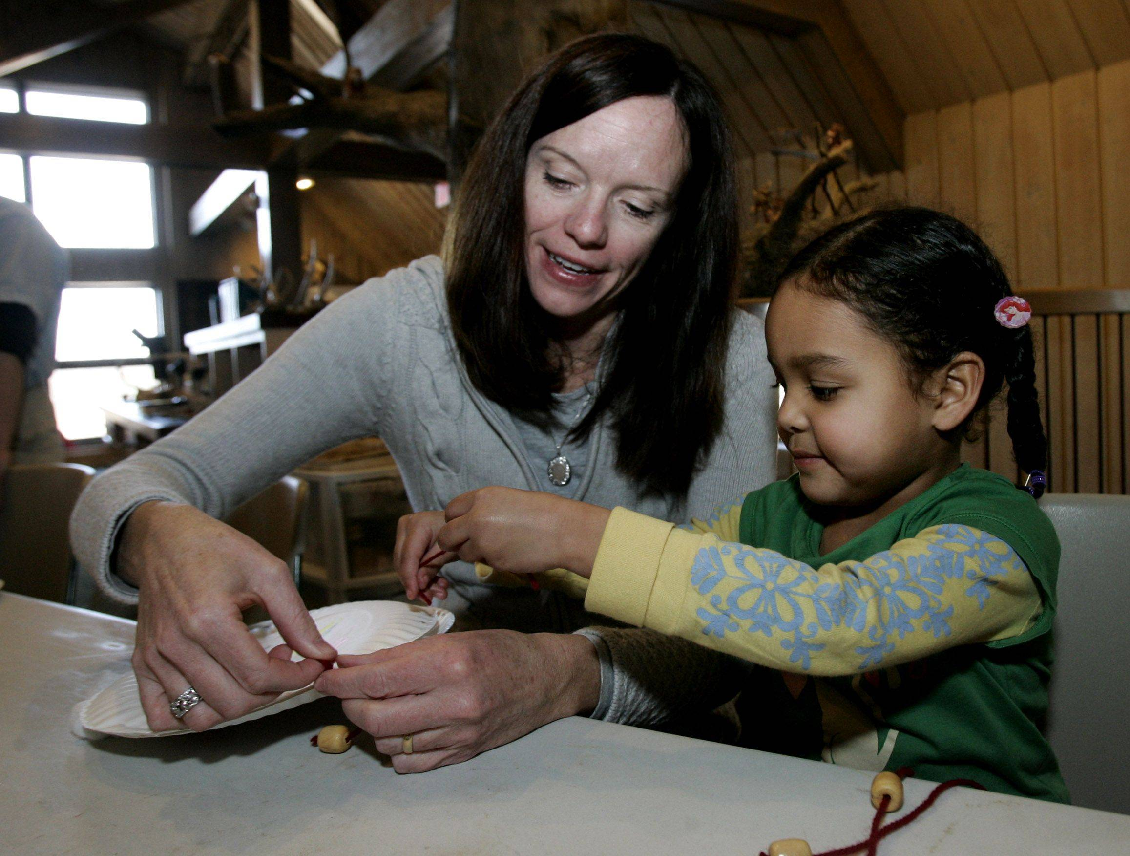 Patty Blake and her daughter Riley, 4, of Mundelein make a paper drum with beads during the annual Volo Bog Winterfest Sunday at Volo Bog State Natural Area.