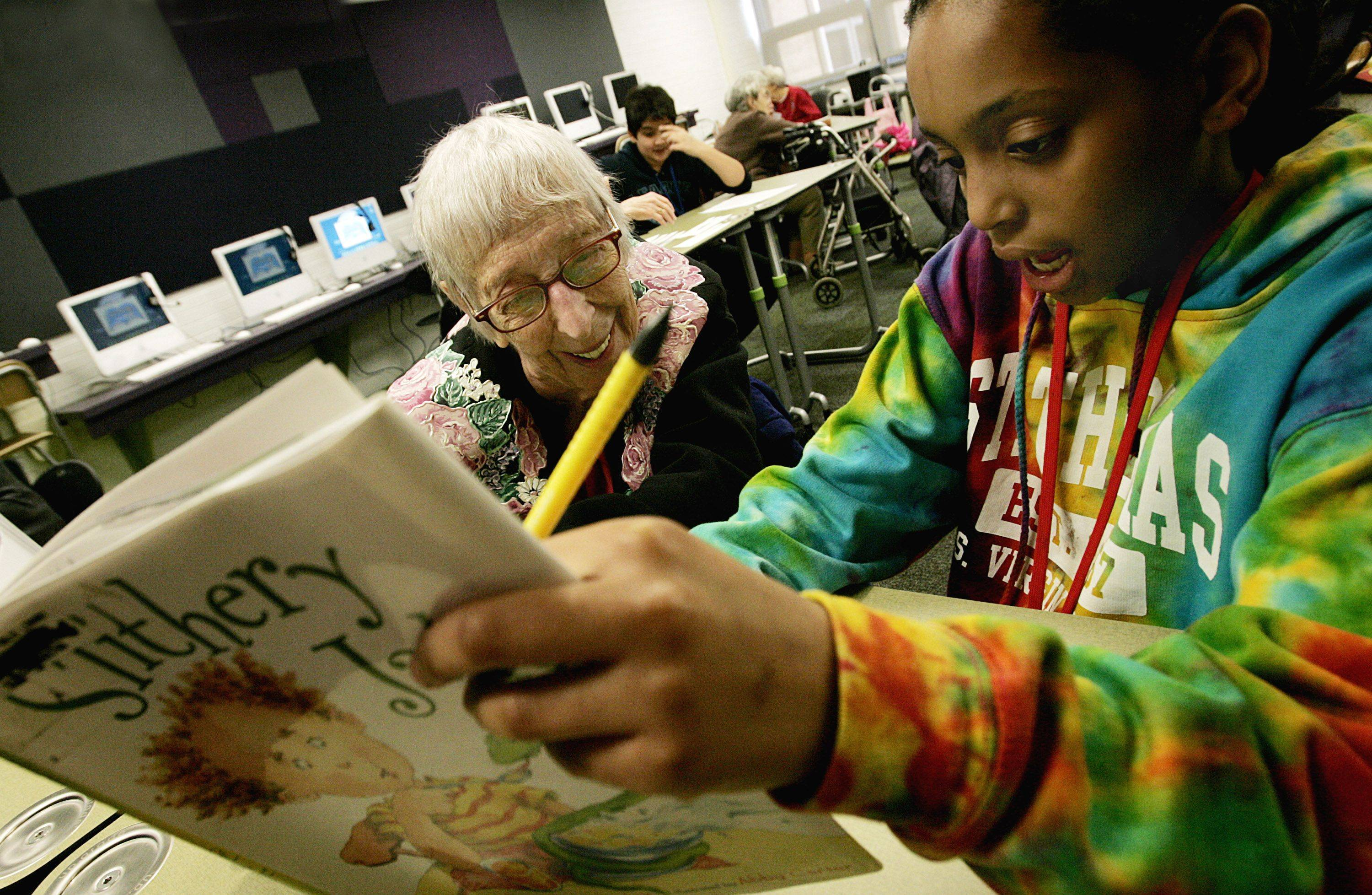 Glen Crest Middle School sixth grader Sydney Johnston, right, reads for senior Jennie Ritzner, left, during their bi-monthly reading session at the school in Glen Ellyn.