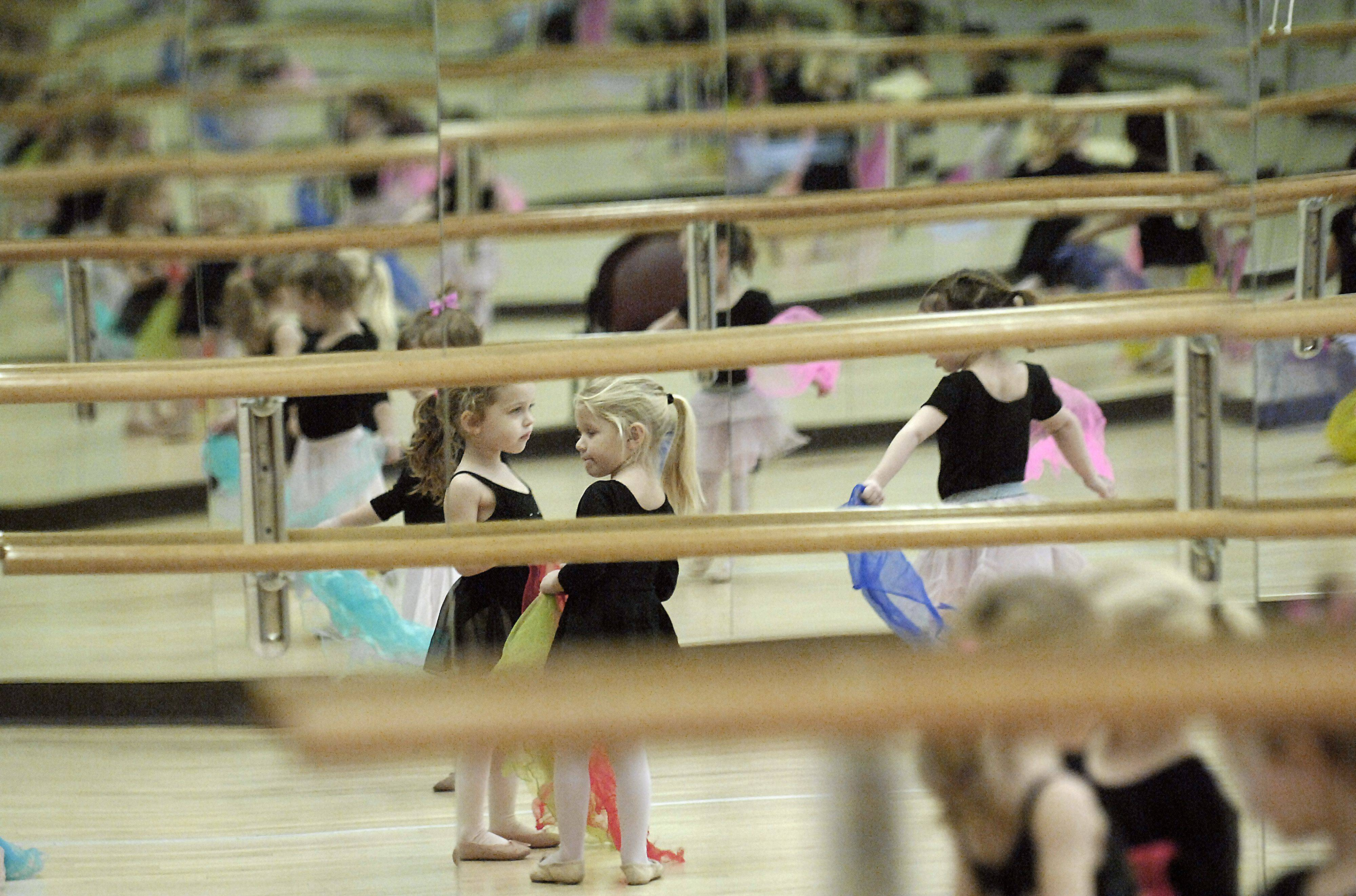 Tori Kallenbach, 4, of South Elgin, left, and Megan Liska, 3, of St. Charles wait to dance with brightly colored scarves in their Babes in Ballet class taught by Debbie Studdard at the St. Charles Park District's Pottawatomie Community Center on Thursday, January 13. This is Tori's second ballet class and Megan's first. Babes in Ballet is offered to age groups starting at age three up and up to six, and several classes are offered during the week.