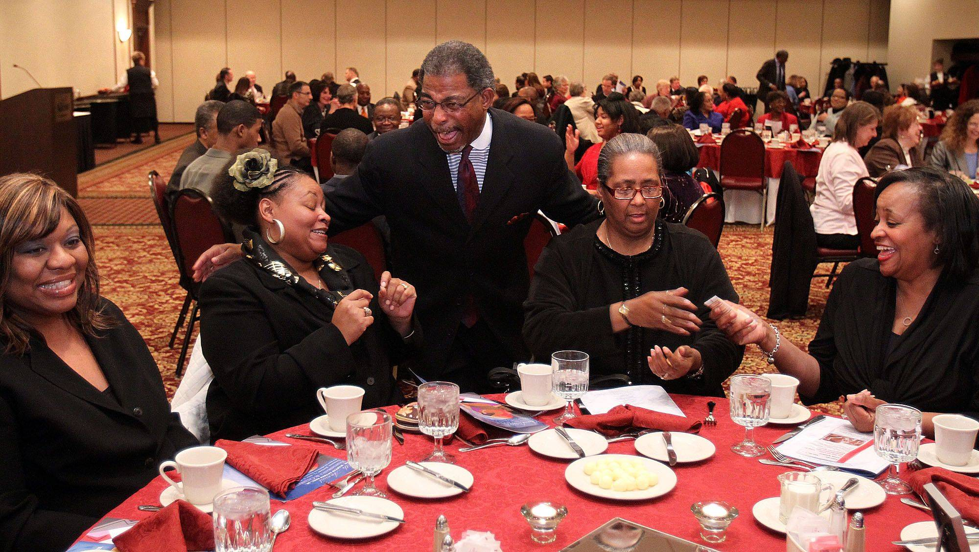 Reverend Nathaniel Edmond, pastor at Second Baptist Church in Elgin, greets each guest at a table at the Illinois Commission on Diversity and Human Relations 10th annual Martin Luther King Jr. dinner at Chicago Marriott Northwest in Hoffman Estates on Thursday, January 13.