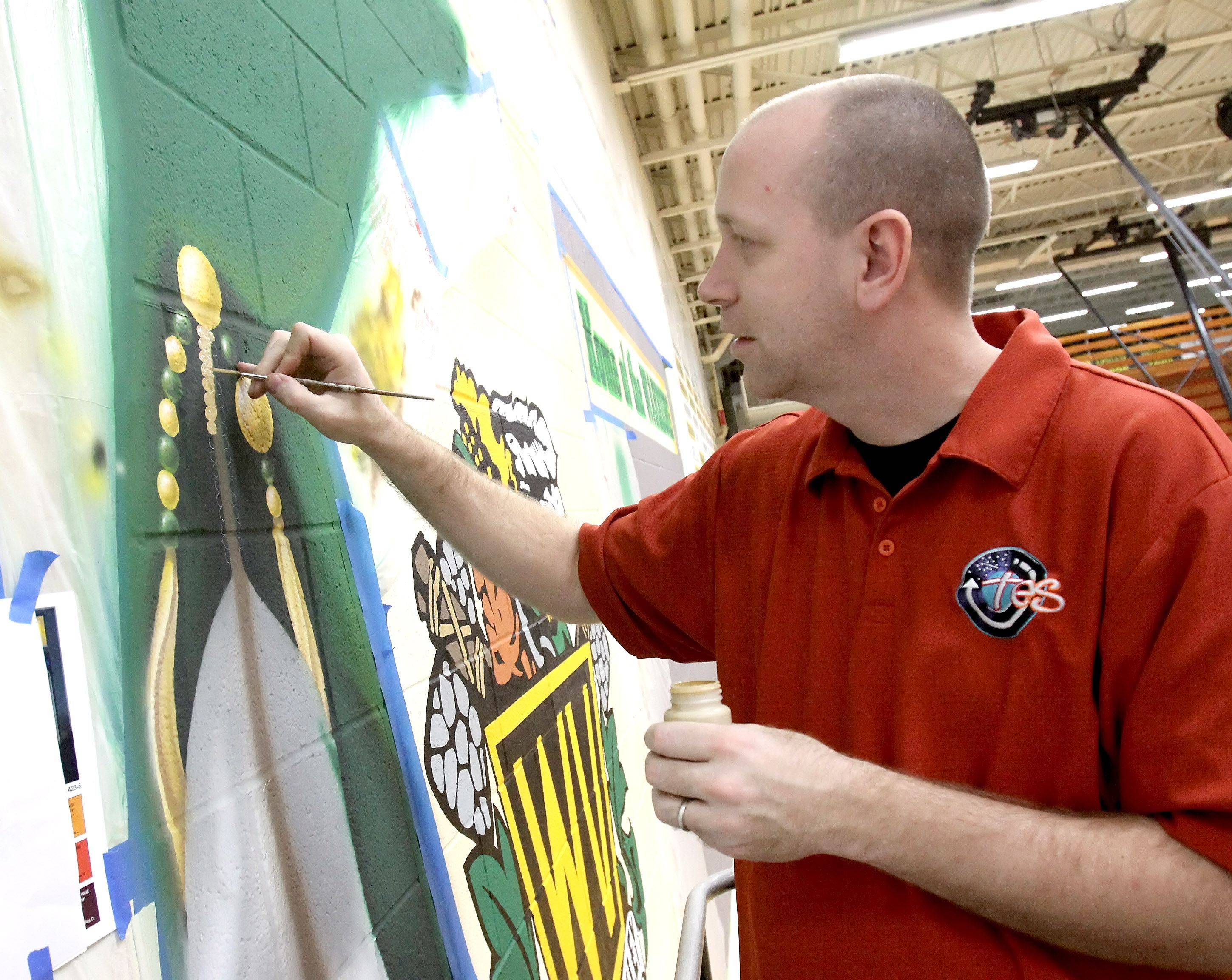 Timm Etters paints a mural at Waubonsie Valley High School in Aurora on Friday. The mural was requested in for the class of 2007 and will be finished this month.