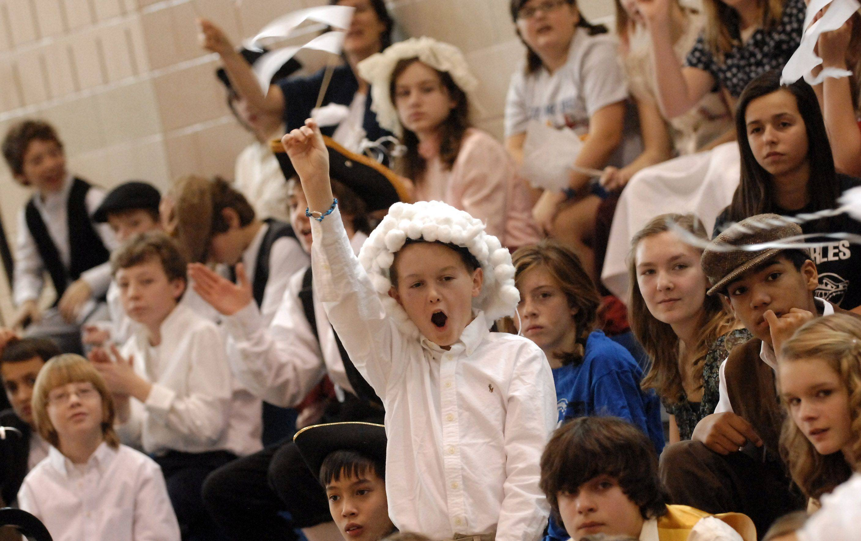 "7th-grader Garrett Otto cheers on the ""white"" team during the quizzer competition at Geneva Middle School North's Patriot Day program Friday."