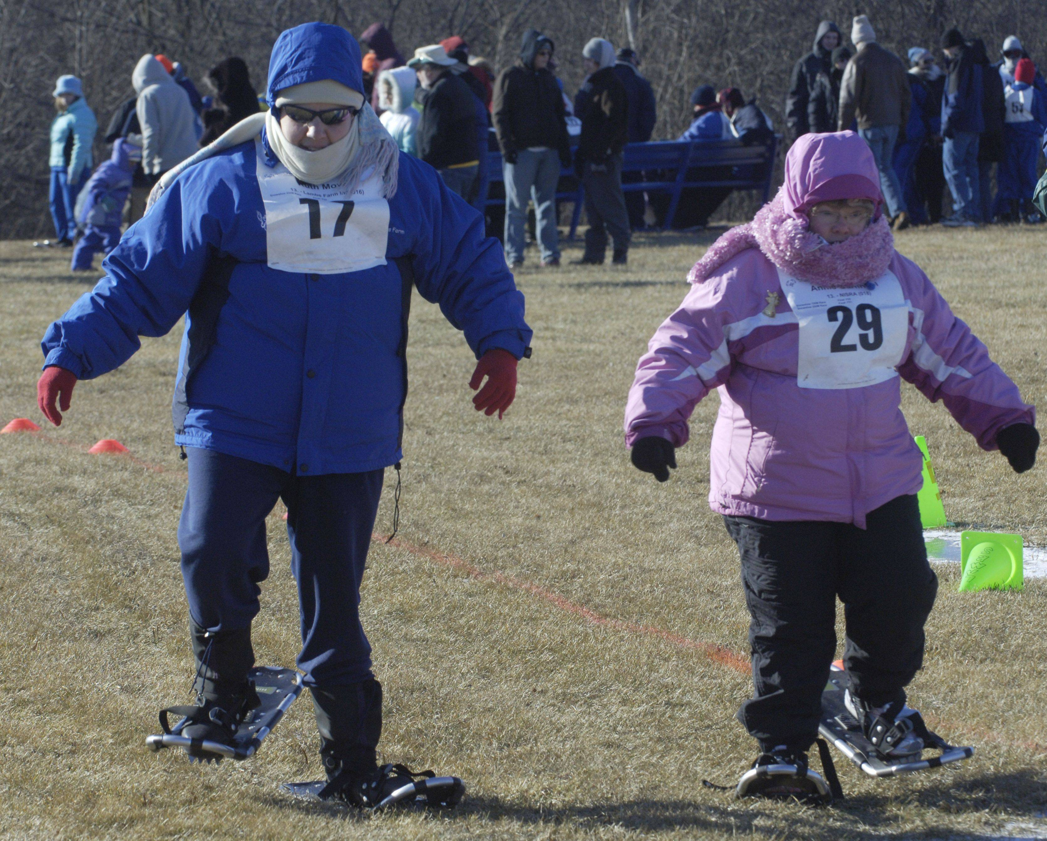Lambs Farm employee Ruth Moyer, left, and Annie Garfinkel of NISRA race during the Special Olympics snowshoeing event.