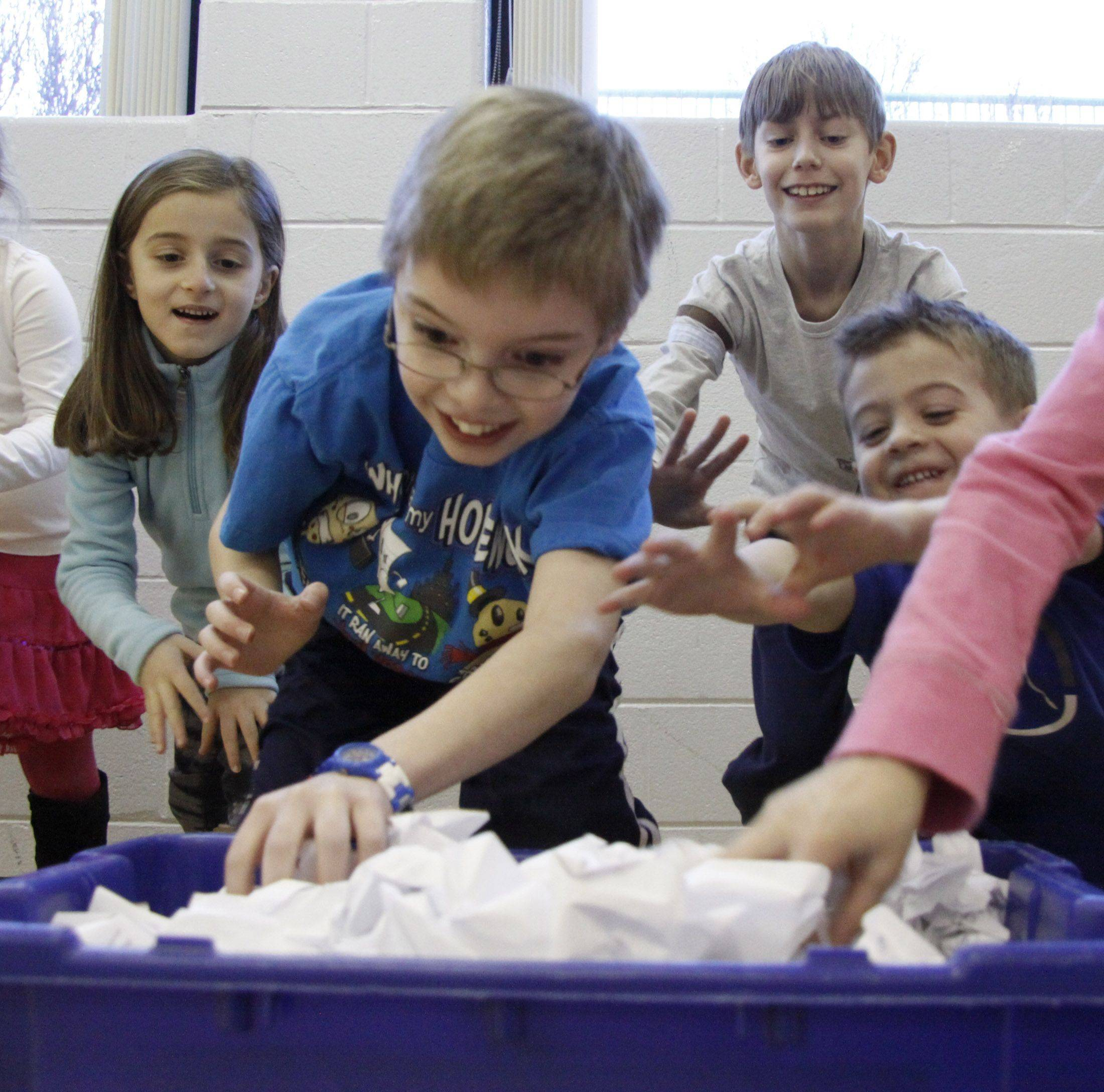 Anna Pahopos, 6, left, Kyle Doogan, 9, Cory Hone, 9, and Nicholas Gironda, right, run to get the snowballs, made of crumpled paper, to throw at the other team at the Indoor Snow Day Saturday at the Clauss Recreation Center in Roselle.