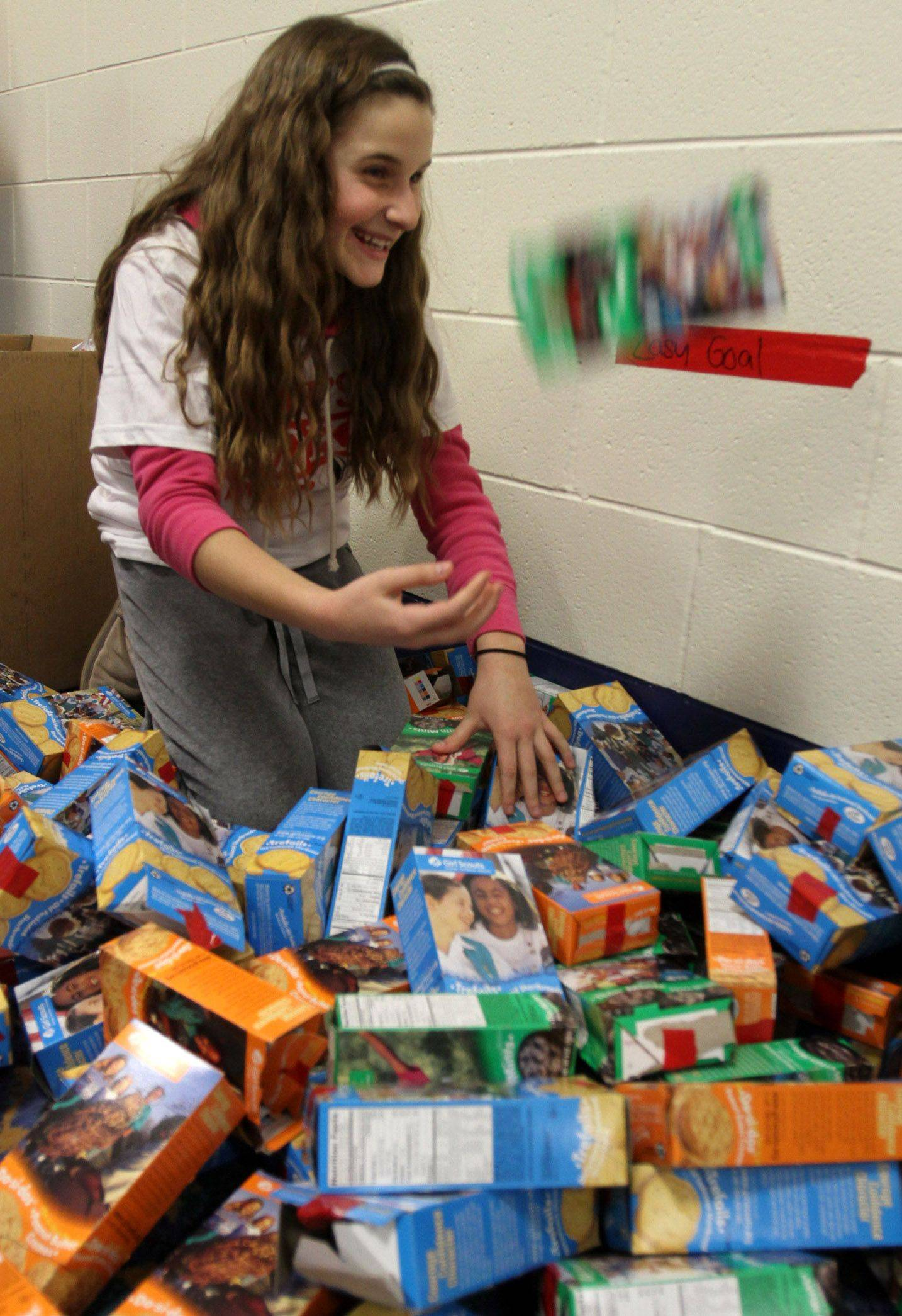 Girl Scout Julia Mills, 10, of Arlington Heights tosses a cookie box after trying to stack as many as she could before the pep rally at Allstate Arena in Rosemont on Saturday, January 8.
