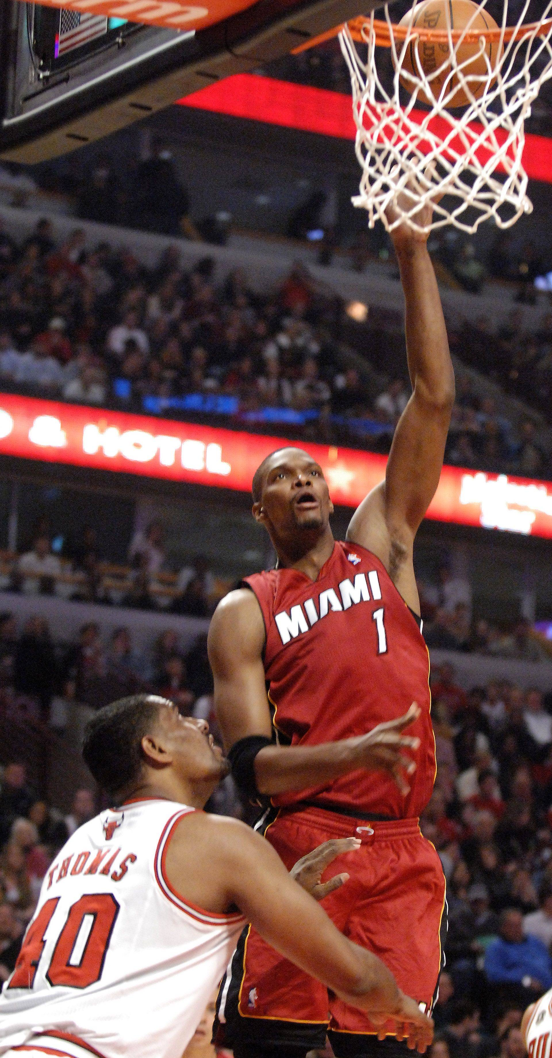 Miami Heat power forward Chris Bosh scores over Chicago Bulls center Kurt Thomas during Saturday's game at the United Center in Chicago.