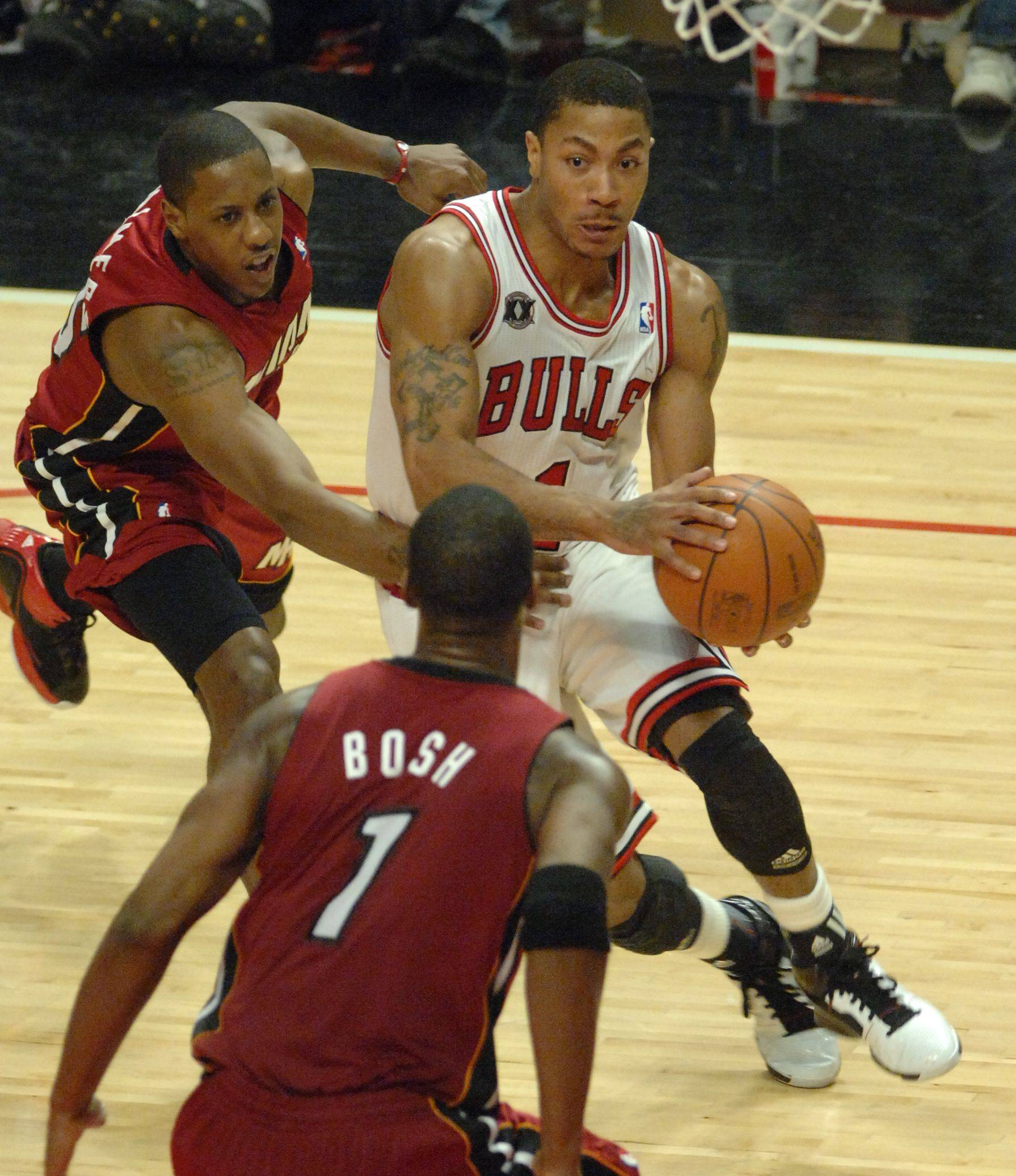 Derrick Rose drives to the basket in the third quarter past Mario Chalmers and into Chirs Bosh during Saturday's game at the United Center against the Miami Heat.