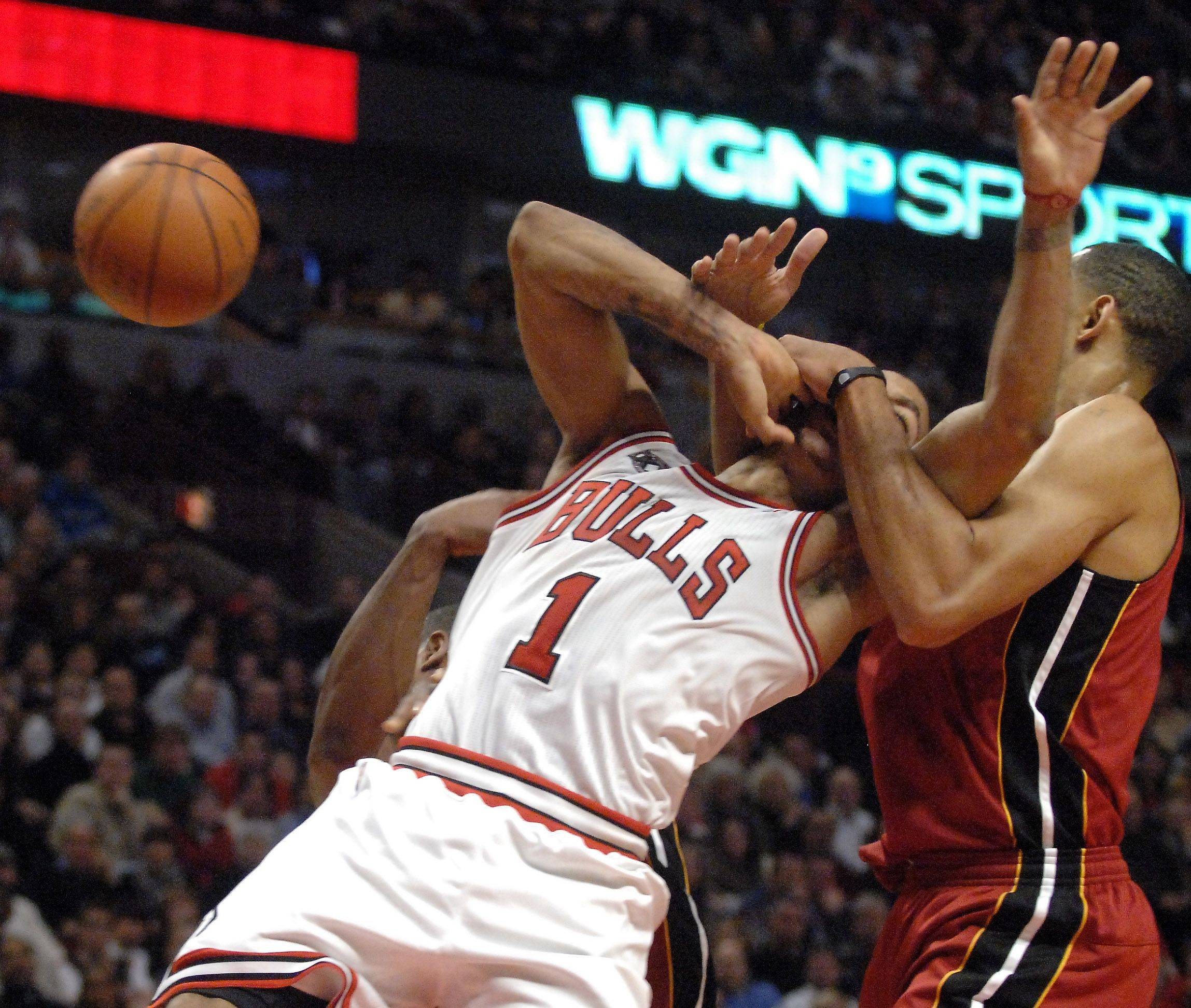 Chicago Bulls point guard Derrick Rose is fouled hard by Miami Heat power forward Juwan Howard during Saturday's game at the United Center in Chicago.