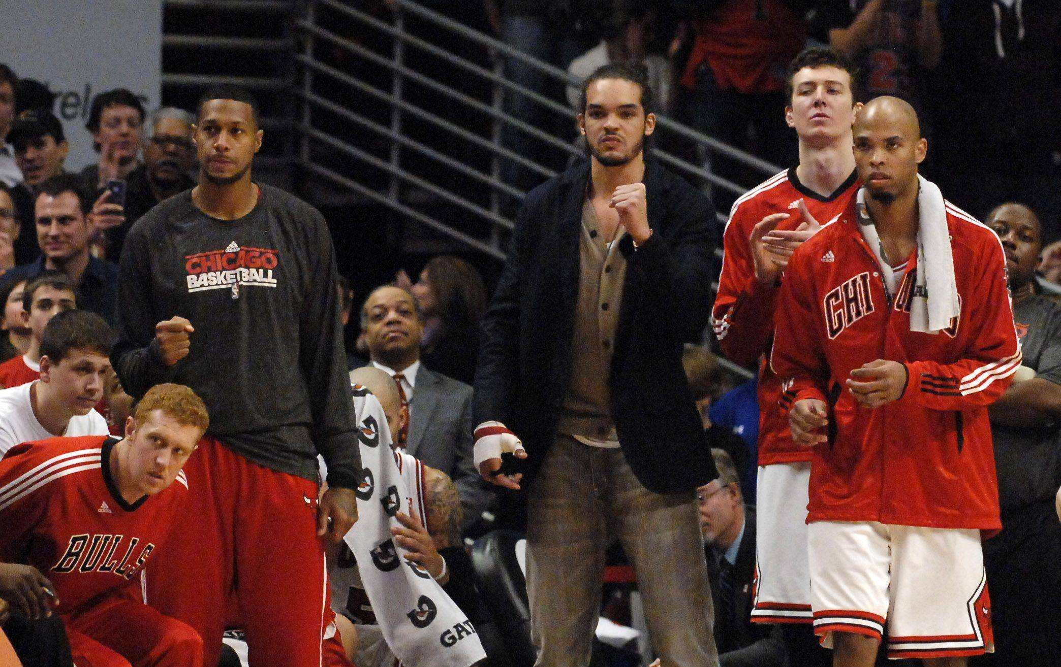 The Bulls bench, including Joakim Noah (in street clothes) watch Ronnie Brewer make a free throw in the final seconds during Saturday's game at the United Center in Chicago.