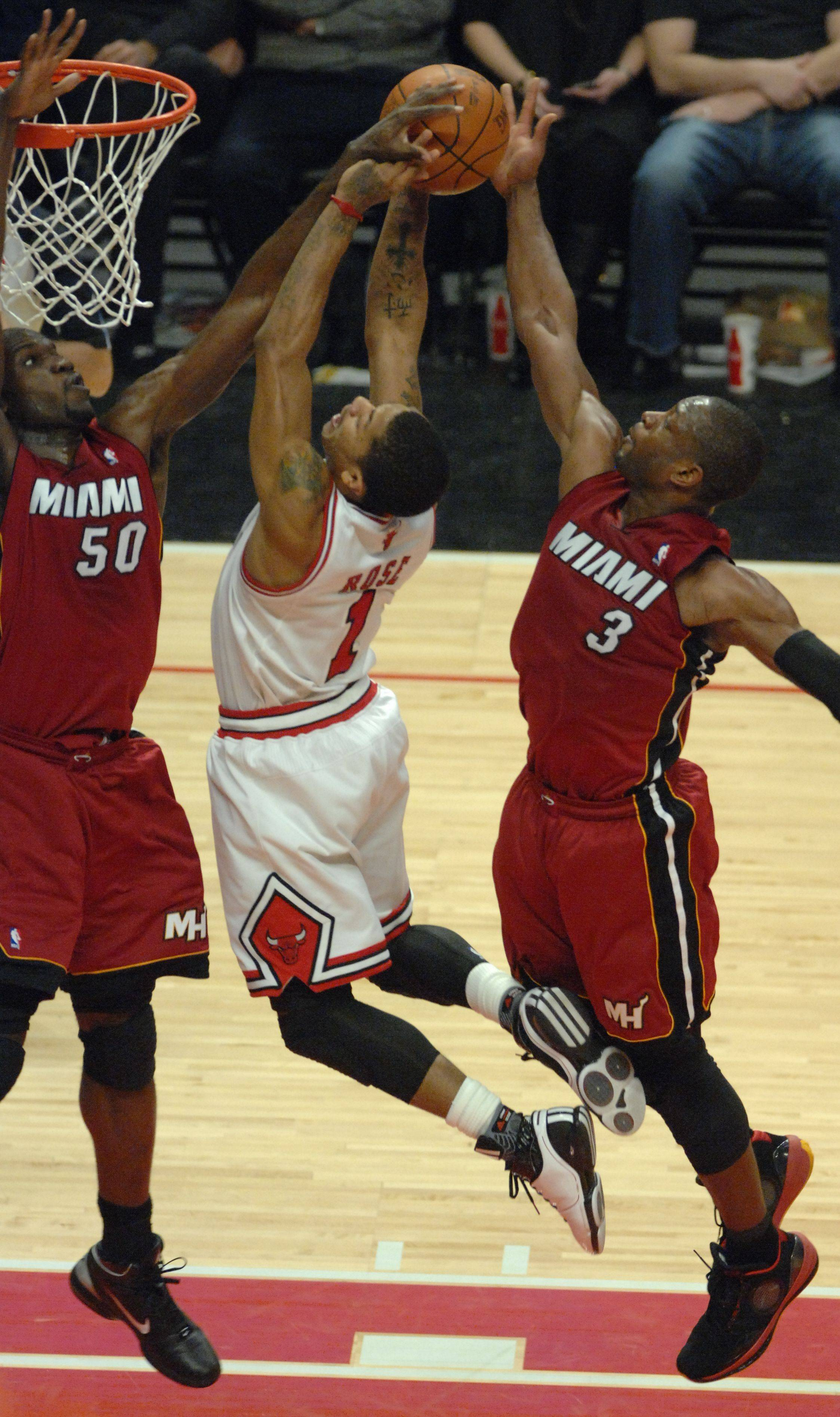 Derrick Rose drives to the basket while surrounded by the Heat's Joel Anthony (50) and Dwyane Wade (3) during Saturday's game at the United Center. Rose finished with 34 points, and Wade had 33 as the Bulls prevailed, 99-96.