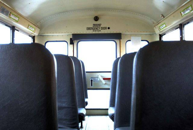There is a camera near the ceiling in the rear of this First Student bus in Naperville.