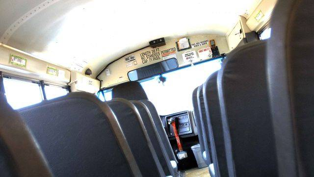 There are two cameras mounted against the ceiling in the front of this First Student bus in Naperville.