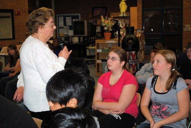 District 96 Twin Groves eighth-graders Emily Magid, left, and Katherine Kritzmire listen as Holocaust survivor Magda Brown describes living conditions for prisoners at Auschwitz in 1944.