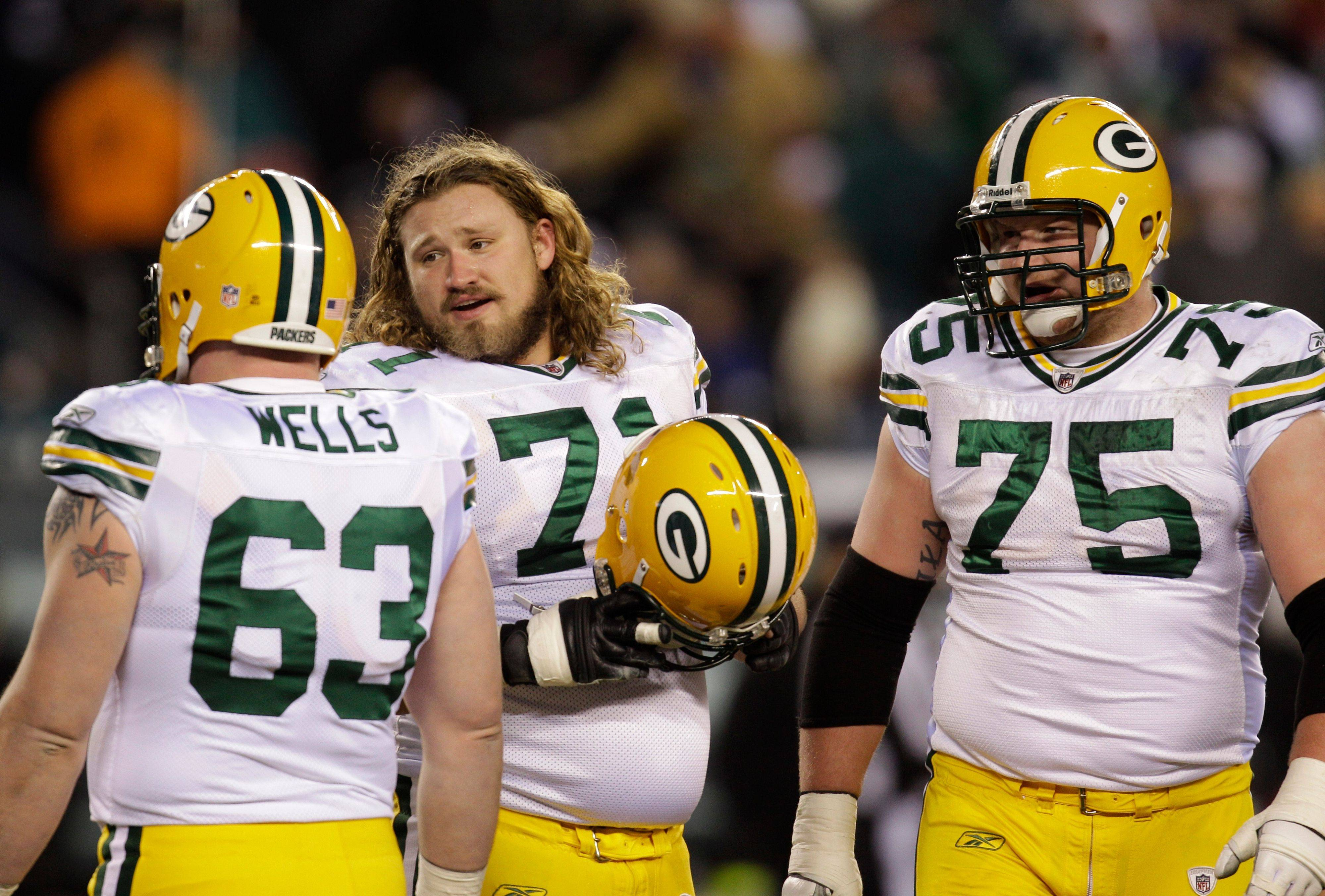 Green Bay Packers center Scott Wells (63) talks with teammates Josh Sitton, center, and Bryan Bulaga (75) during their NFL playoff game against the Philadelphia Eagles in Philadelphia. Bulaga, a rookie first-round pick at offensive tackle, was born in Barrington and grew up in Crystal Lake.