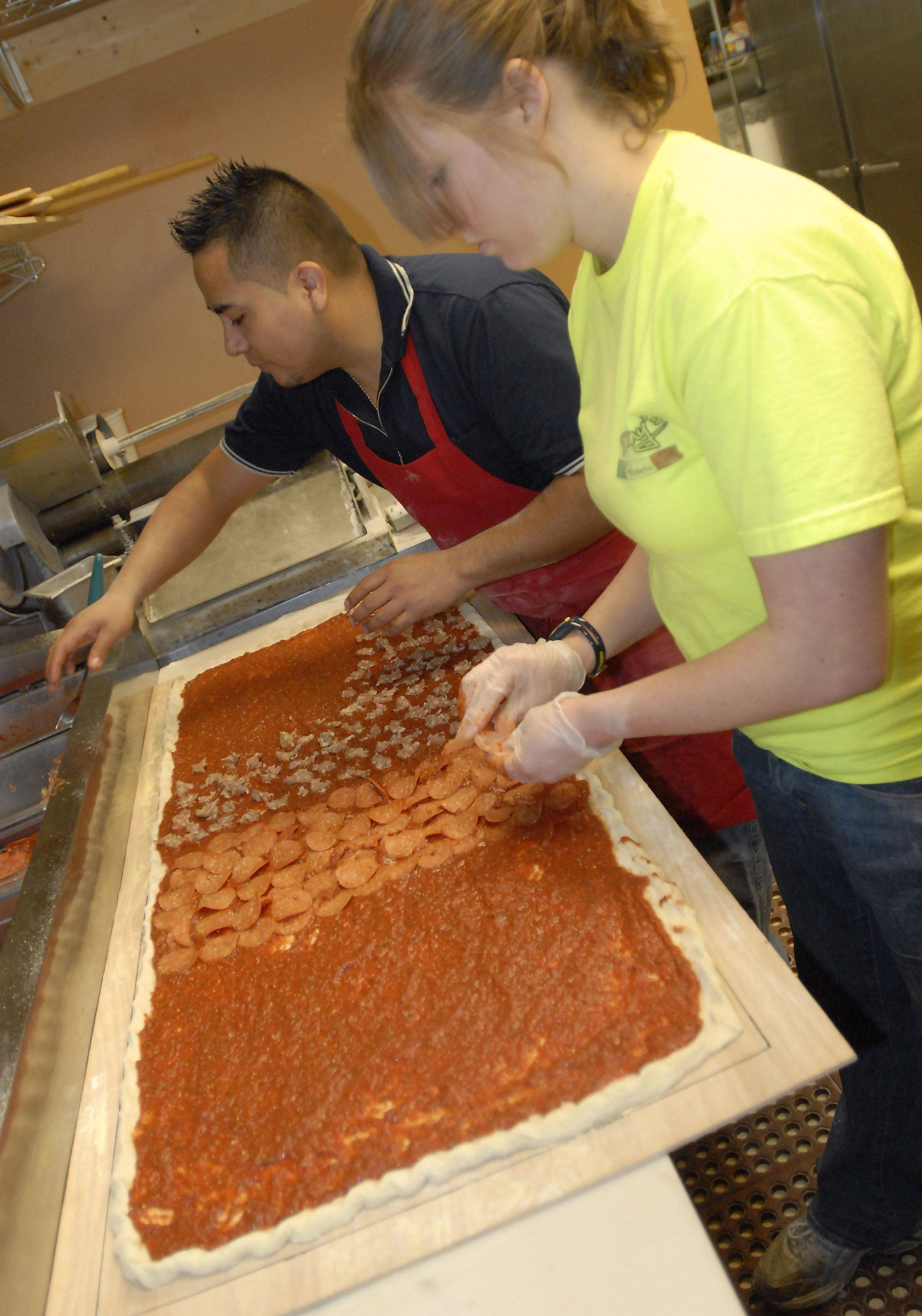 Donny's Pizzeria employees Miguel Morales and Maggie Holm prepare the Epic pizza, 20 by 50 inches.