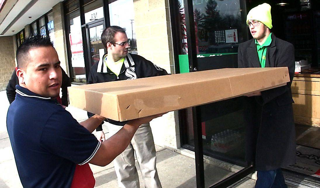 Donny Toole, owner of Donny's Pizzeria in Arlington Heights, holds the door as the 50 inch-long pizza is brought to the delivery van.
