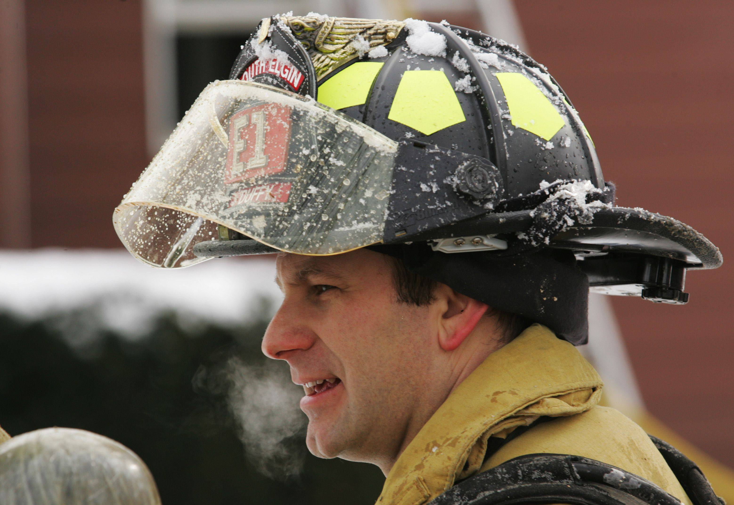 In the chilly winter air Thursday, South Elgin firefighter Paul Duffy talks with other members of his department at the scene of a house fire on Gale Street in Elgin Township.
