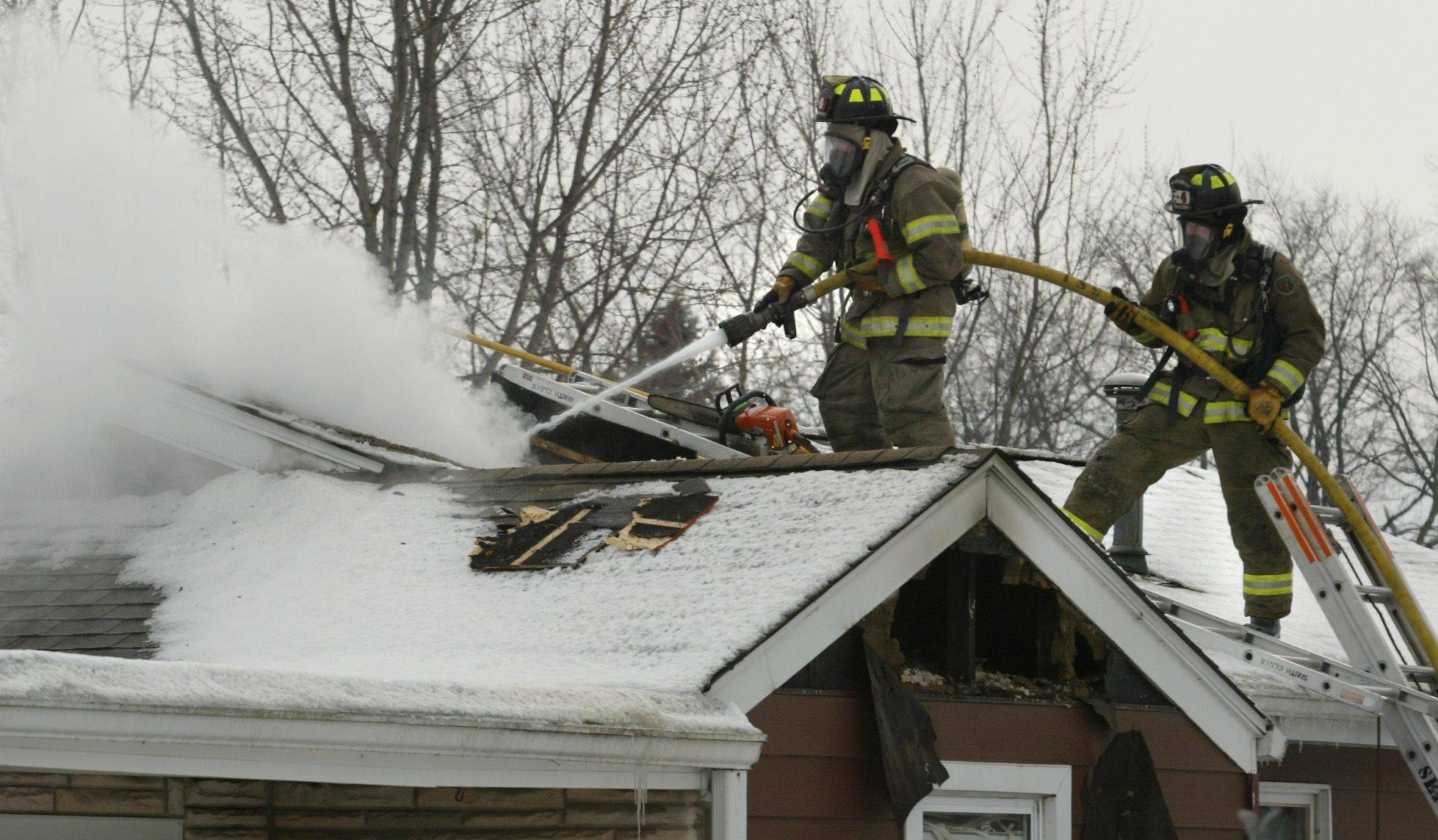 Elgin firefighters Craig Pleva and Curt Hanson help extinguish a fire in the attic of a home Thursday in Elgin Township.