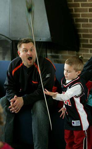 Rob Ferguson of Mt. Prospect watches his son, Carter Ferguson, 4, balance a peacock feather Saturday during the annual Winter Carnival at the Lombard Community Building.