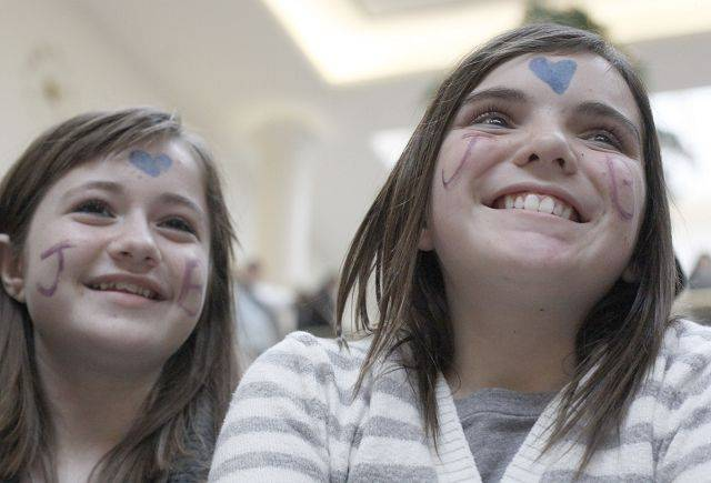 Hayley Huber, 13, right, and Kiara McGee, 13, both of Wheaton listen to fans sing songs by Justin Bieber Saturday at the Yorktown Center in Lombard. Fans were competing against one another in hopes of winning a trip to L.A. and a chance to meet the pop star.