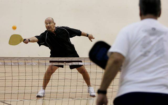 Tom Baumann, 70 reaches for the ball as seniors from the Del Webb community in Mundelein play pickleball Tuesday at the Libertyville Sports Complex.