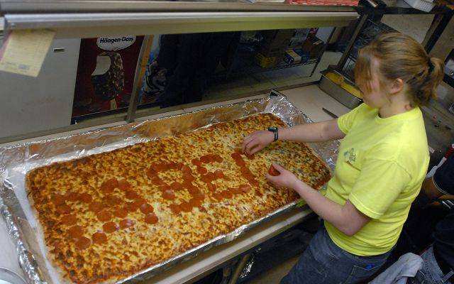 Donny's Pizzeria employee Maggie Holm finishes off a pizza of epic proportions with Da Bears spelled out in pepperoni at their Arlington Heights store. The pizza can feed 40 people and is made with 11 pounds of dough.
