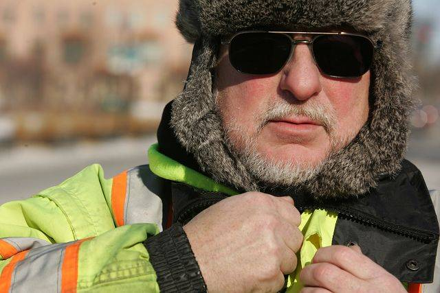 City of Elgin employee Steve Udell zips up his jacket while working outside Friday in single-digit temperatures in downtown Elgin.