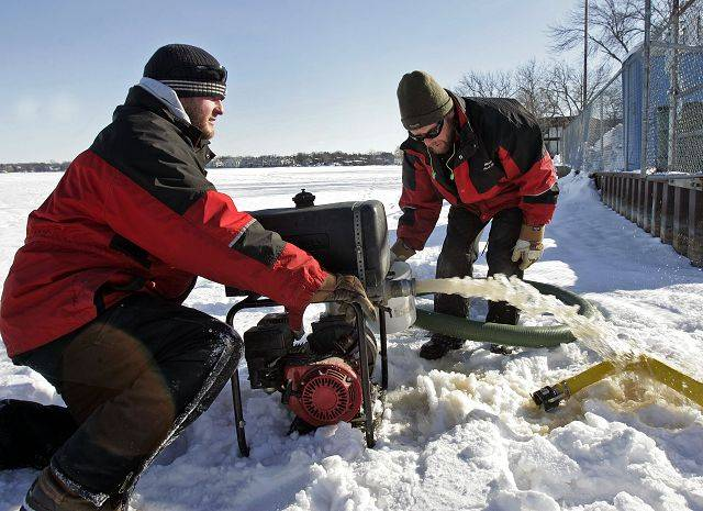 Wauconda park district employees Dave Schwarz and Jack Spears try to get a water pump started after cutting a hole in Bangs lake. The duo had the unenviable task of freezing the hockey rink on Bangs Lake on the coldest day of the year Friday.