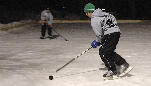 Santino Salamone, 15, of St. Charles, plays a pick-up hockey game on the outdoor skating rink with friends at Wheeler Park in Geneva on Tuesday evening.