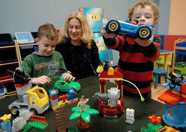 Christian Voelker, 9, owner Lidia Voelker and 3-year-old Austin Waltz play at C&A Robot Factory, which is opening in Libertyville in early February.