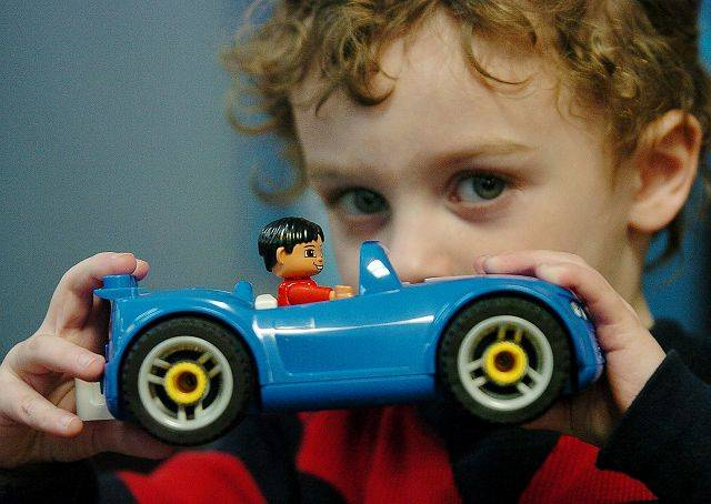 Austin Waltz, 3, holds up his favorite LEGO car at C&A Robot Factory in Libertyville.